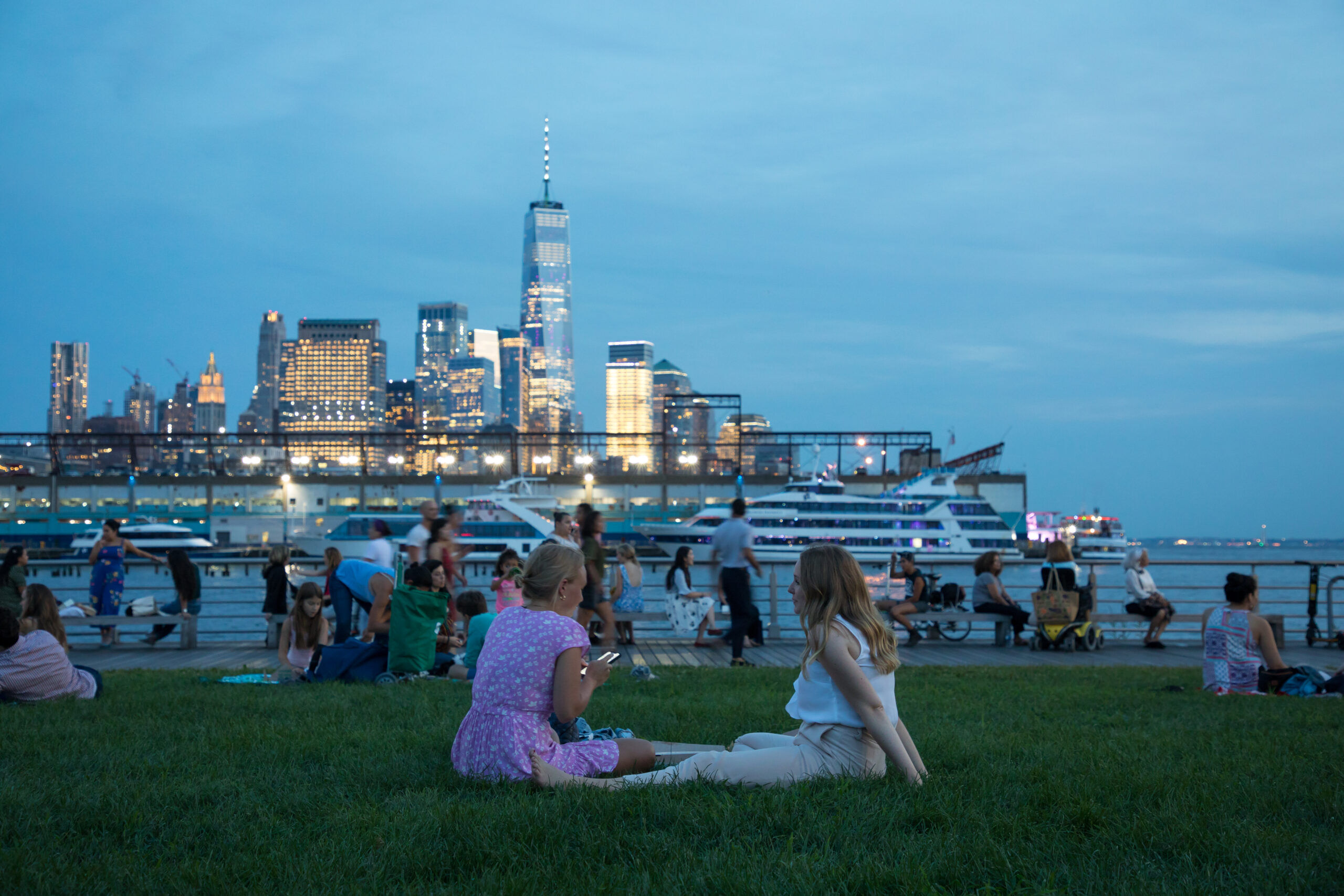 Park visitors rest on the Pier 45 lawn as the sun goes down