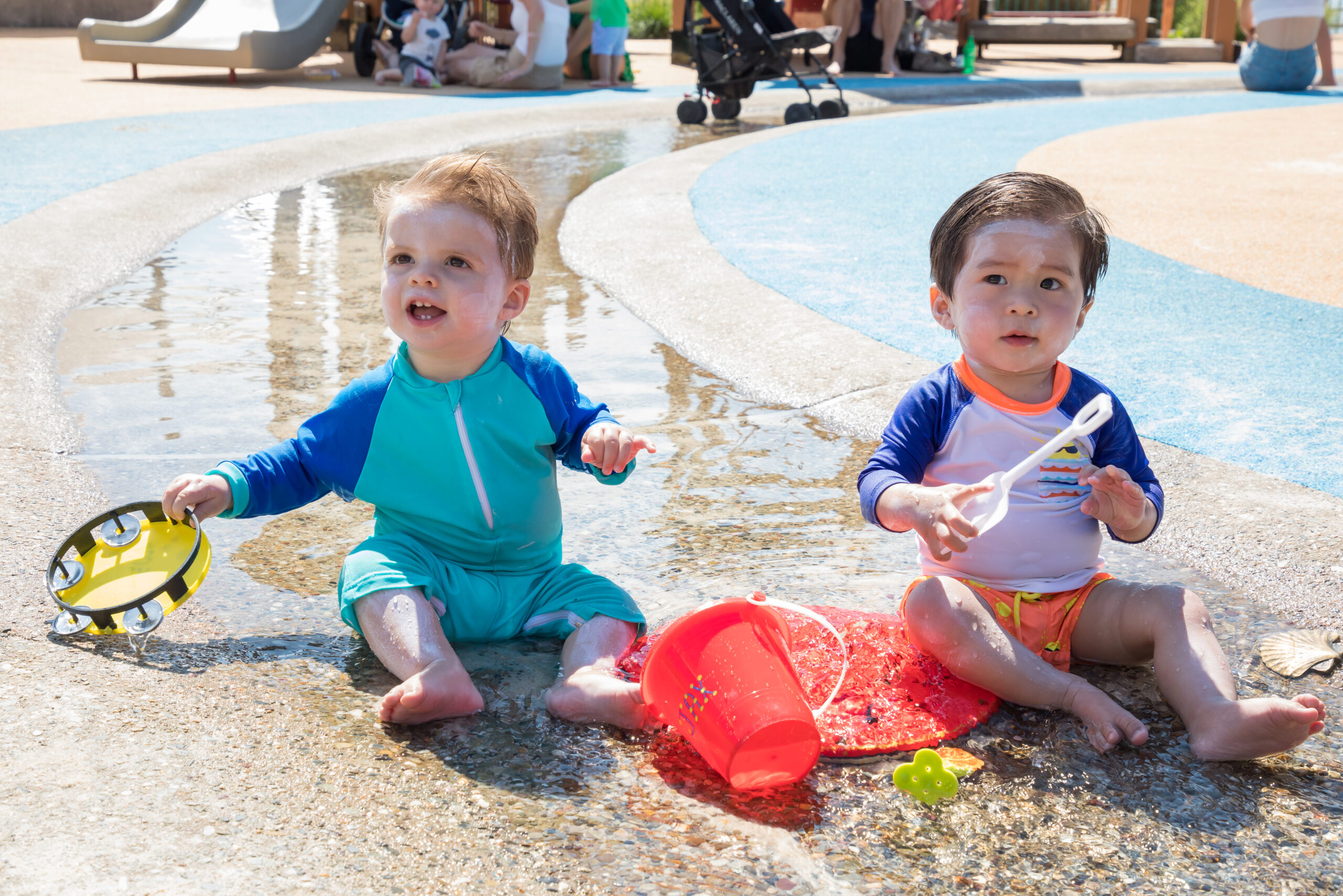Two babies play in the water at Pier 51