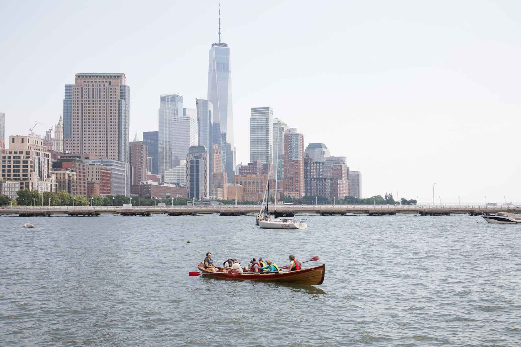 A group grab their paddles and begin rowing in the Hudson River