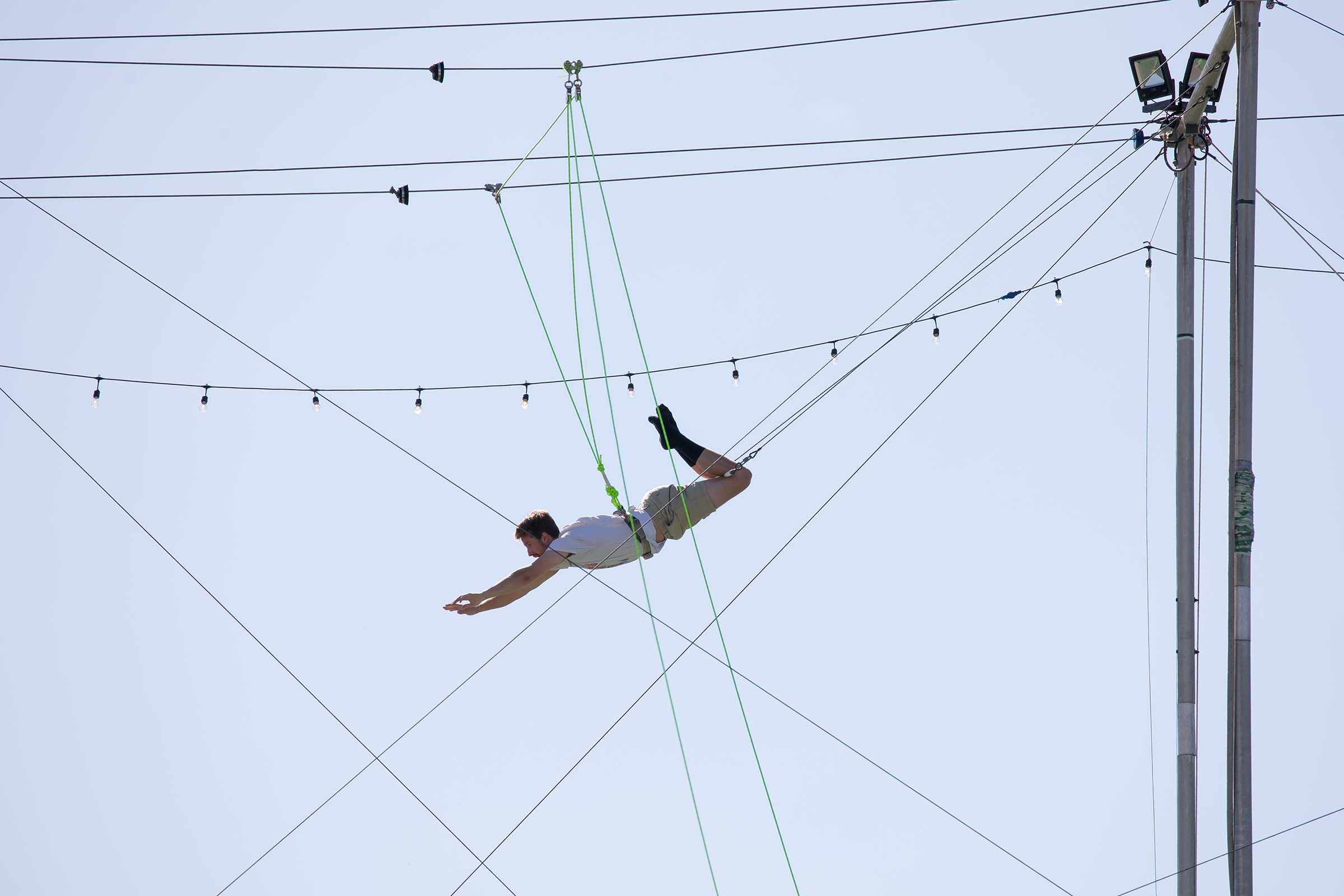 A trapeze artist swings and reaches for the bar in the air