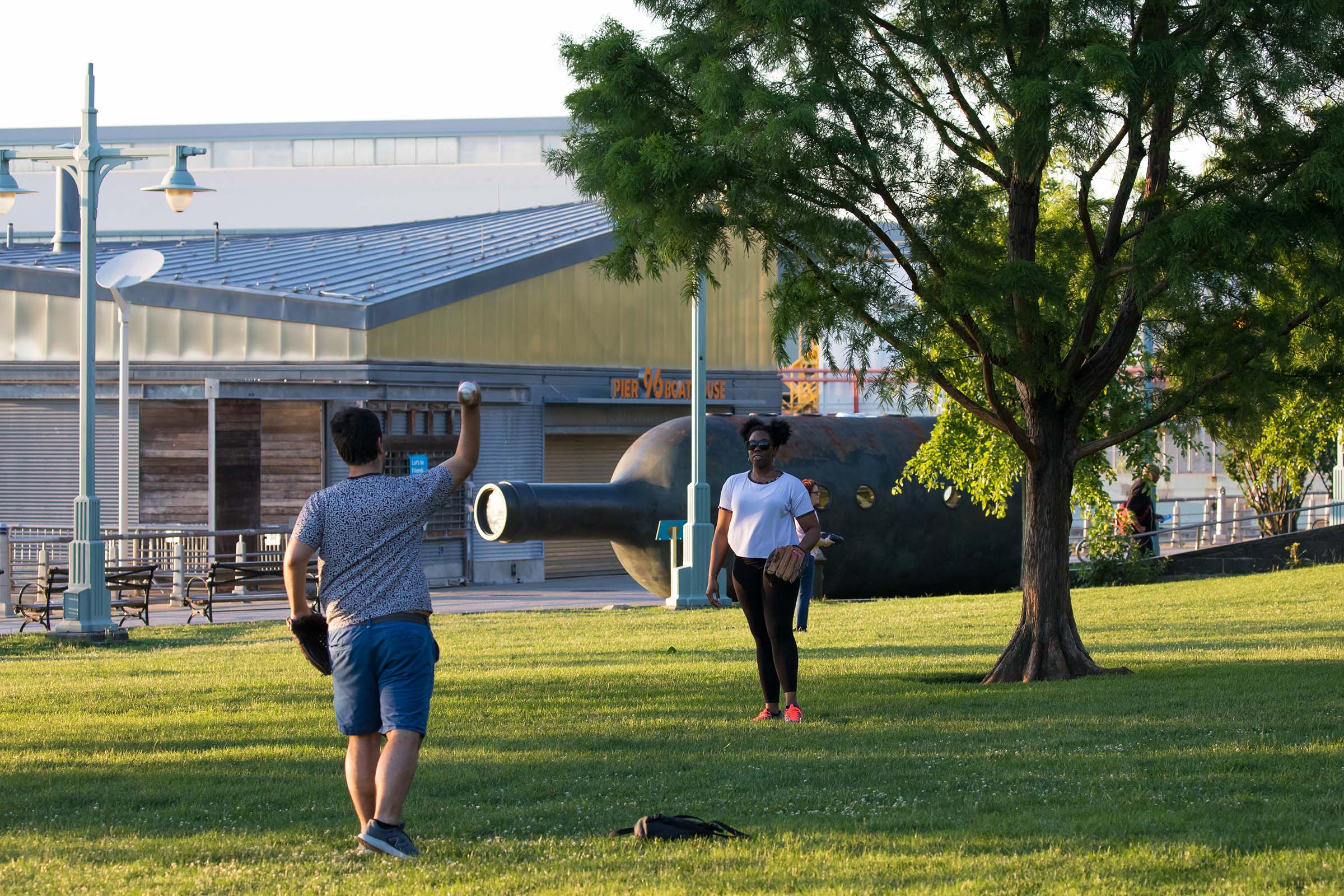 Park visitors throw a baseball on the field near Private Passage