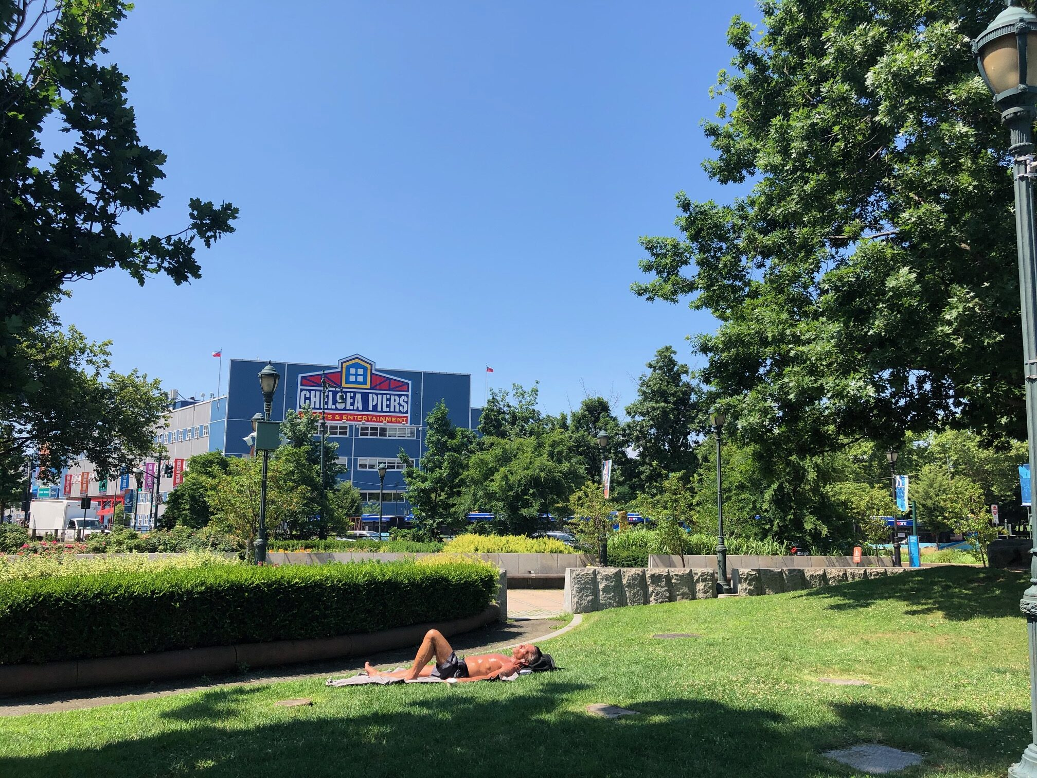 Chelsea Piers building painted blue with the green lawns surrounding it. A sunbather is laying on the grass
