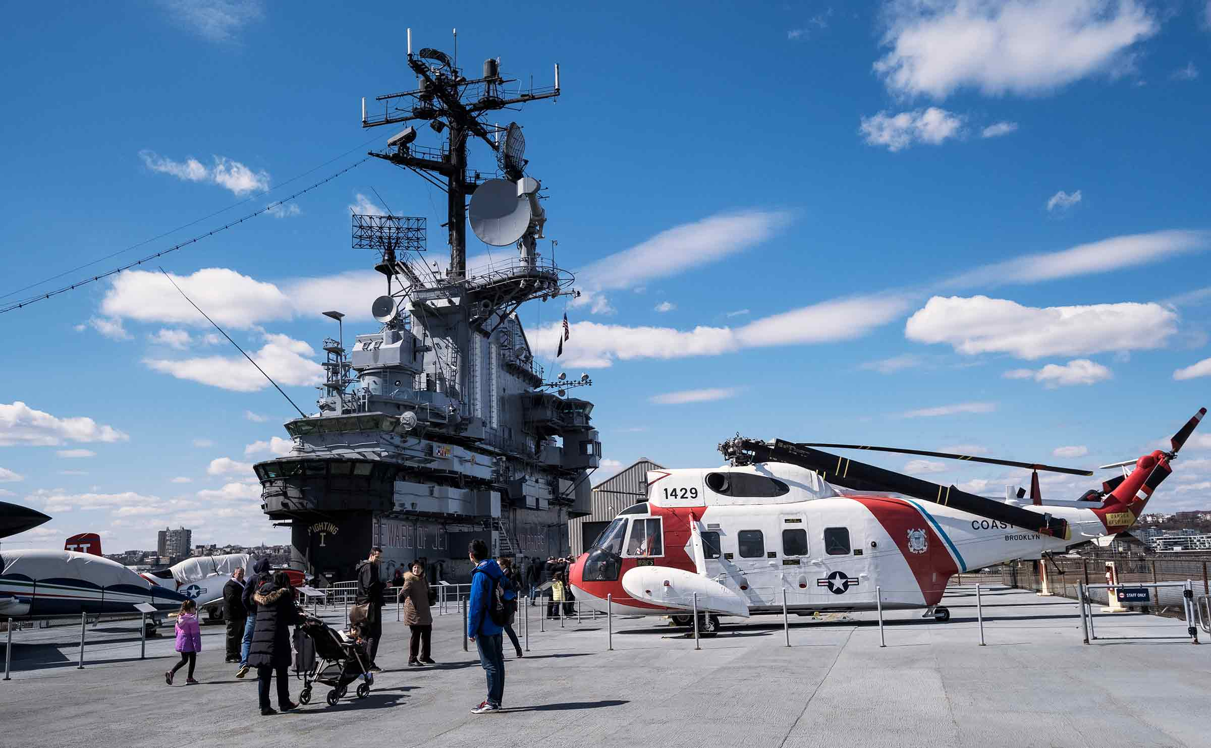 A red and white helicopter sits on the roof of the Intrepid