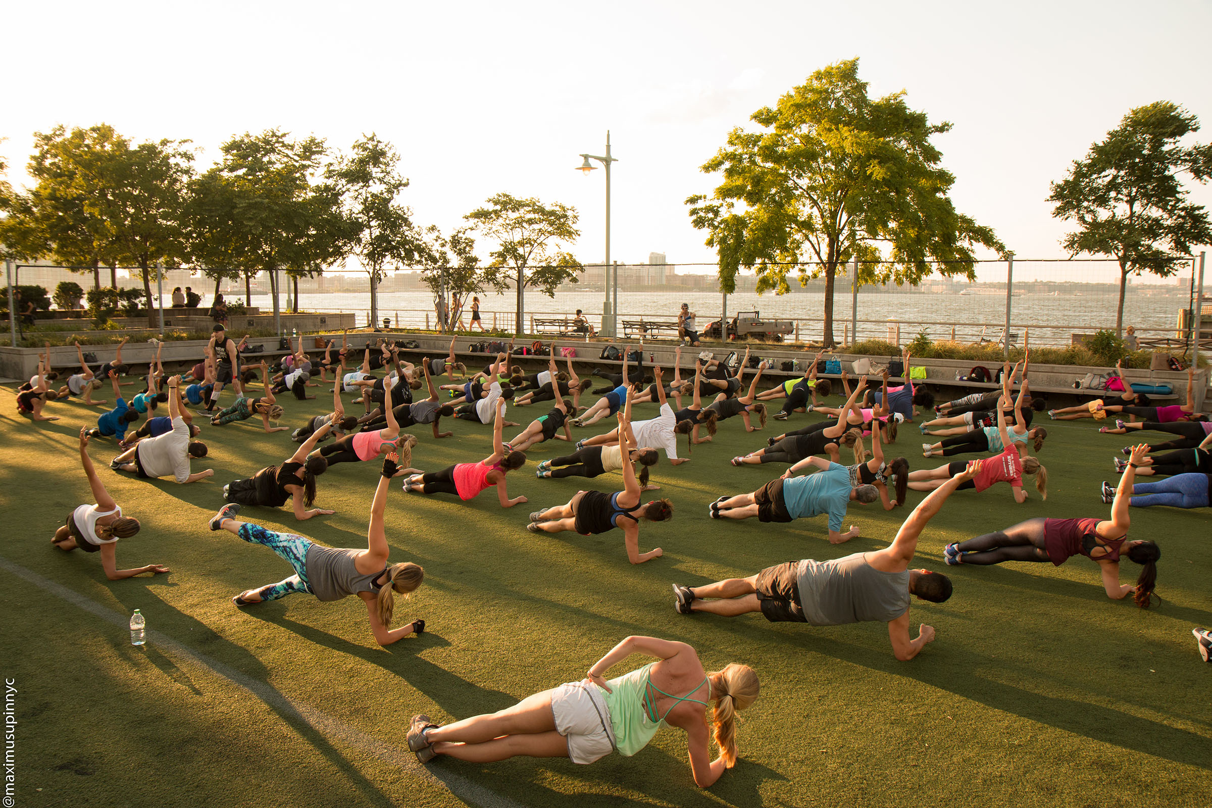 A large group of yoga enthusiasts begin on the lawn at Pier 25
