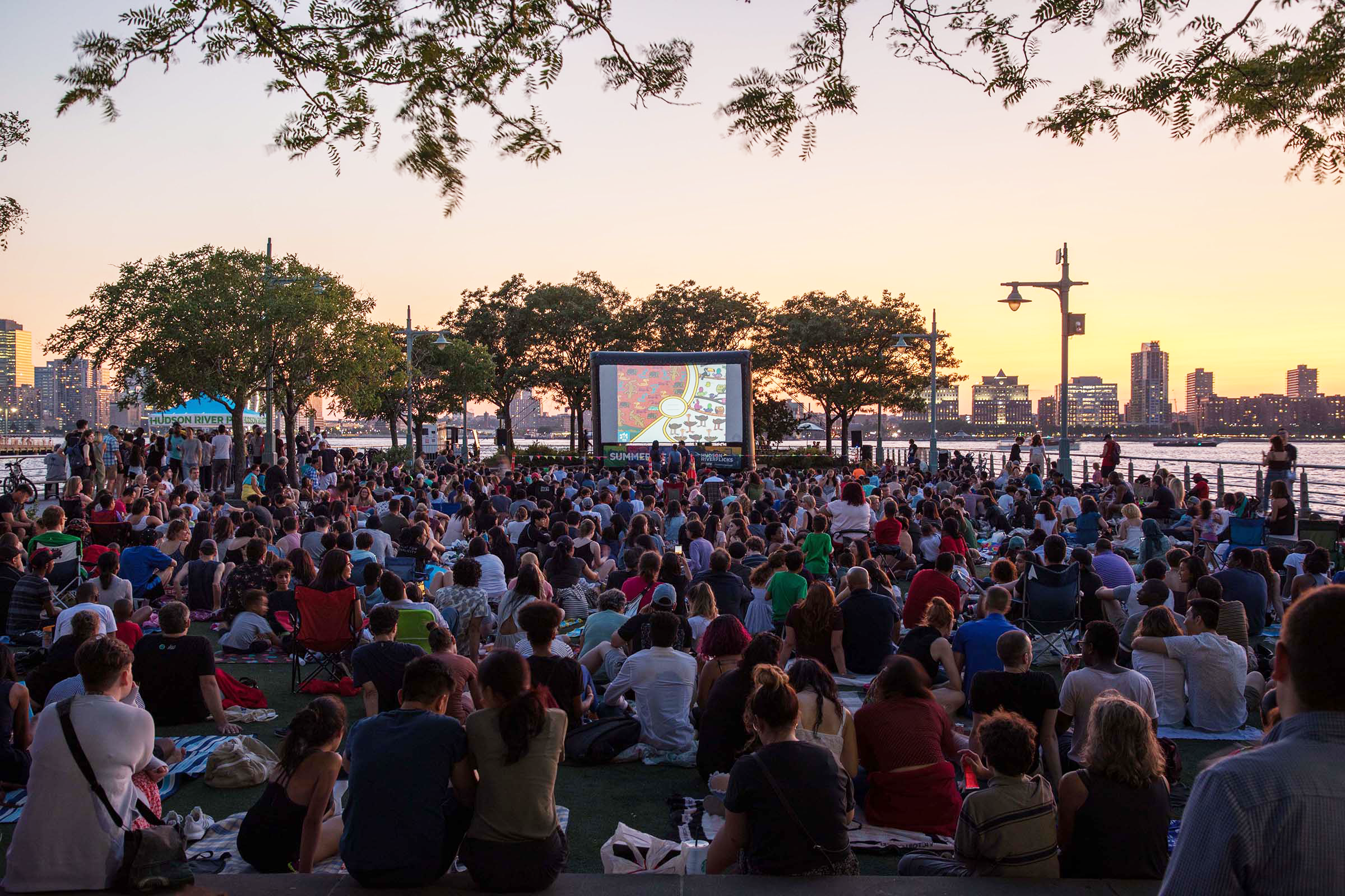 A large group of visitors enjoy the movie at Pier 46