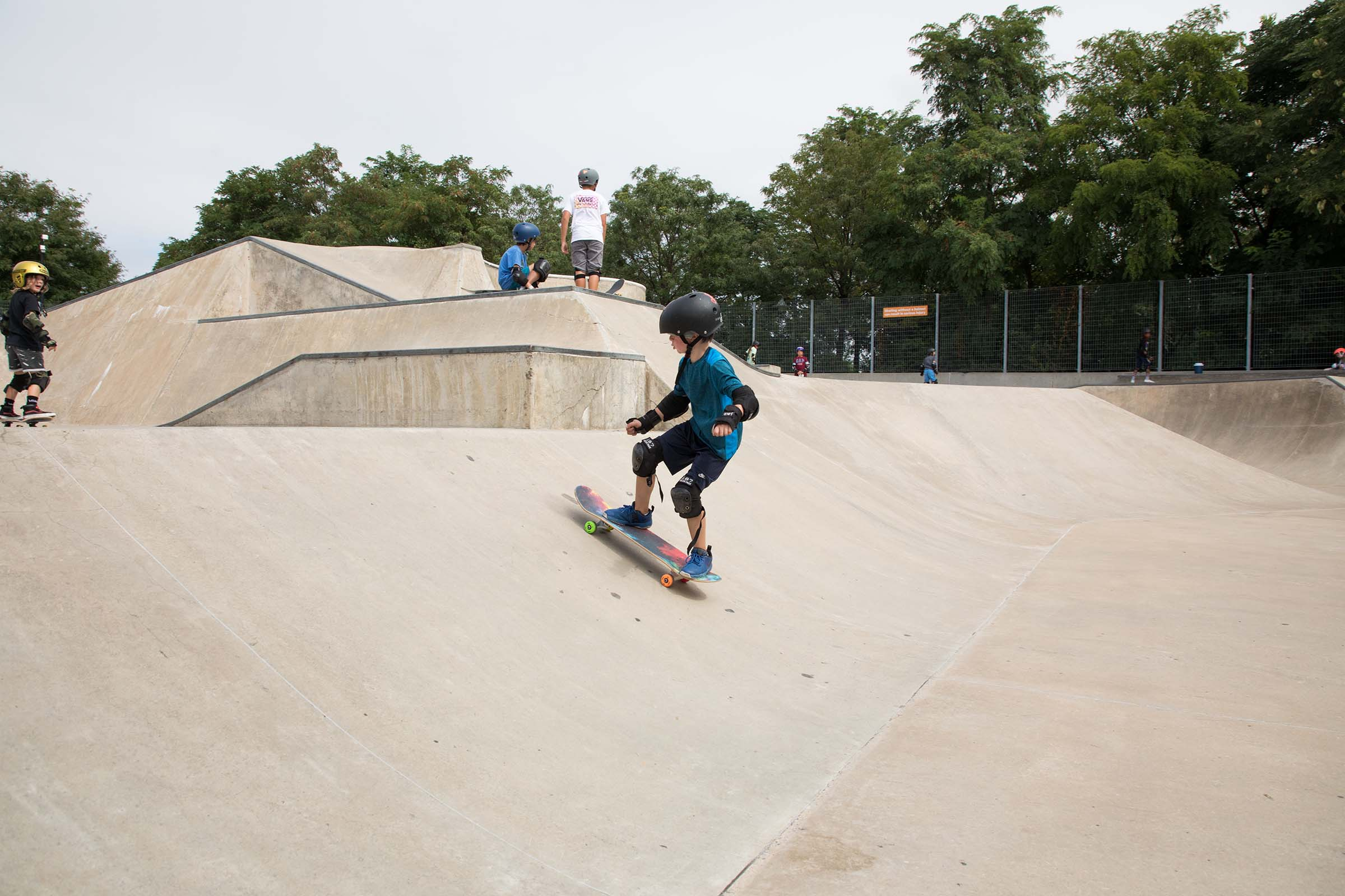 A shot of a kid skateboarder on the diagonal incline at Pier 62's skatepark