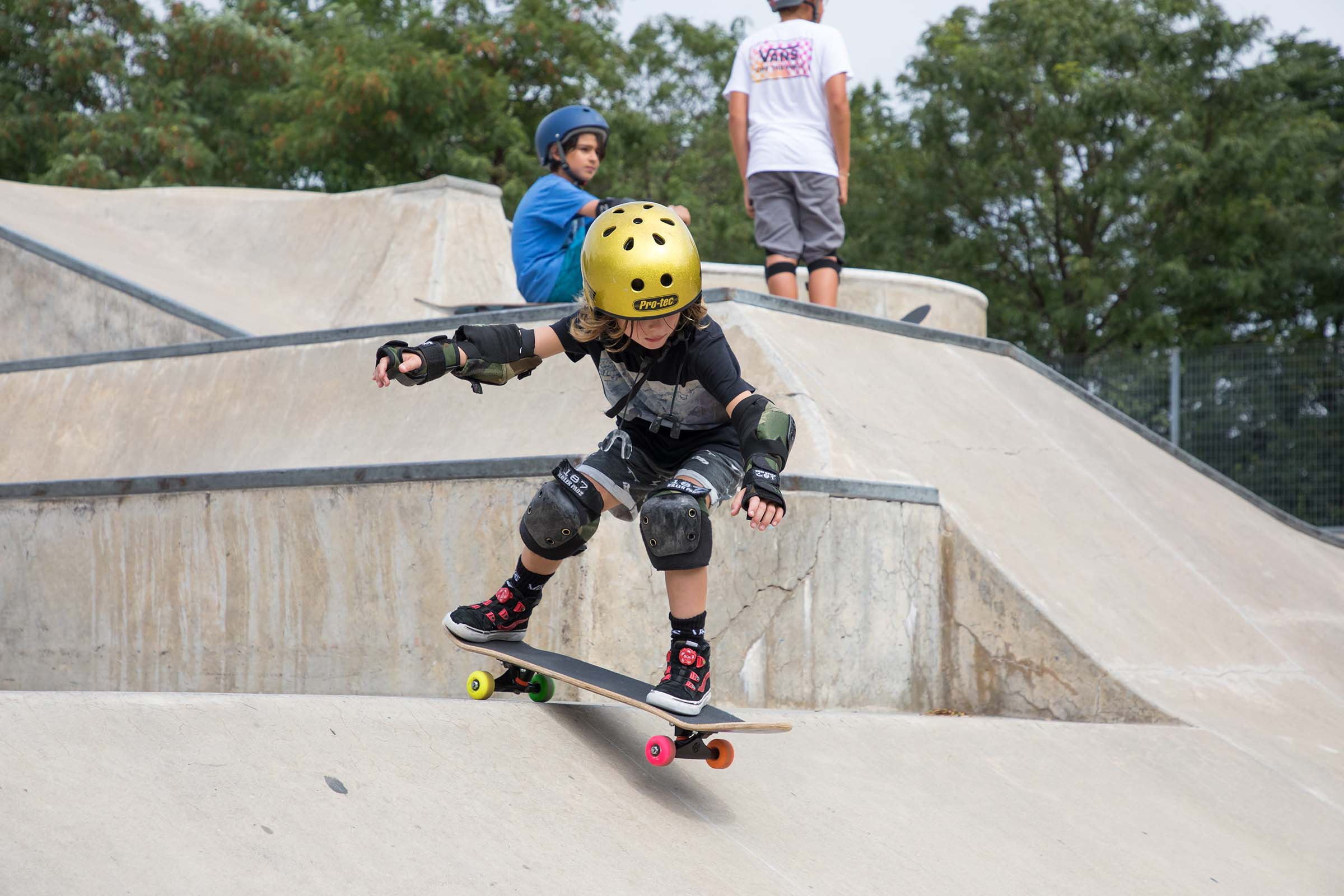 A kid skateboarder in a yellow helmet heads down the incline at Pier 62's Skatepark