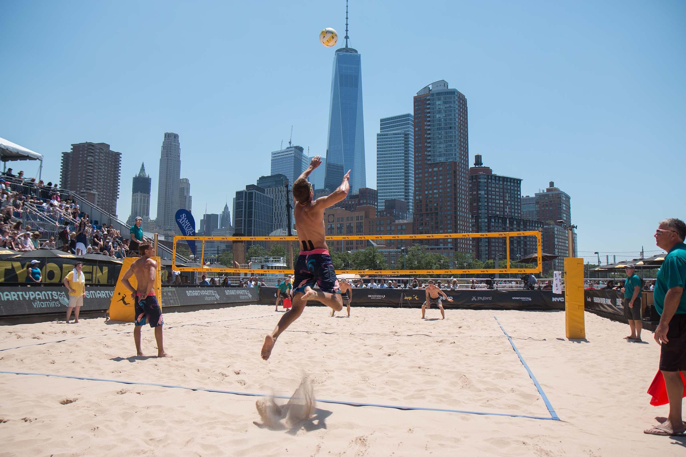 A volleyball player jumps and flies towards the ball to hit it over the net