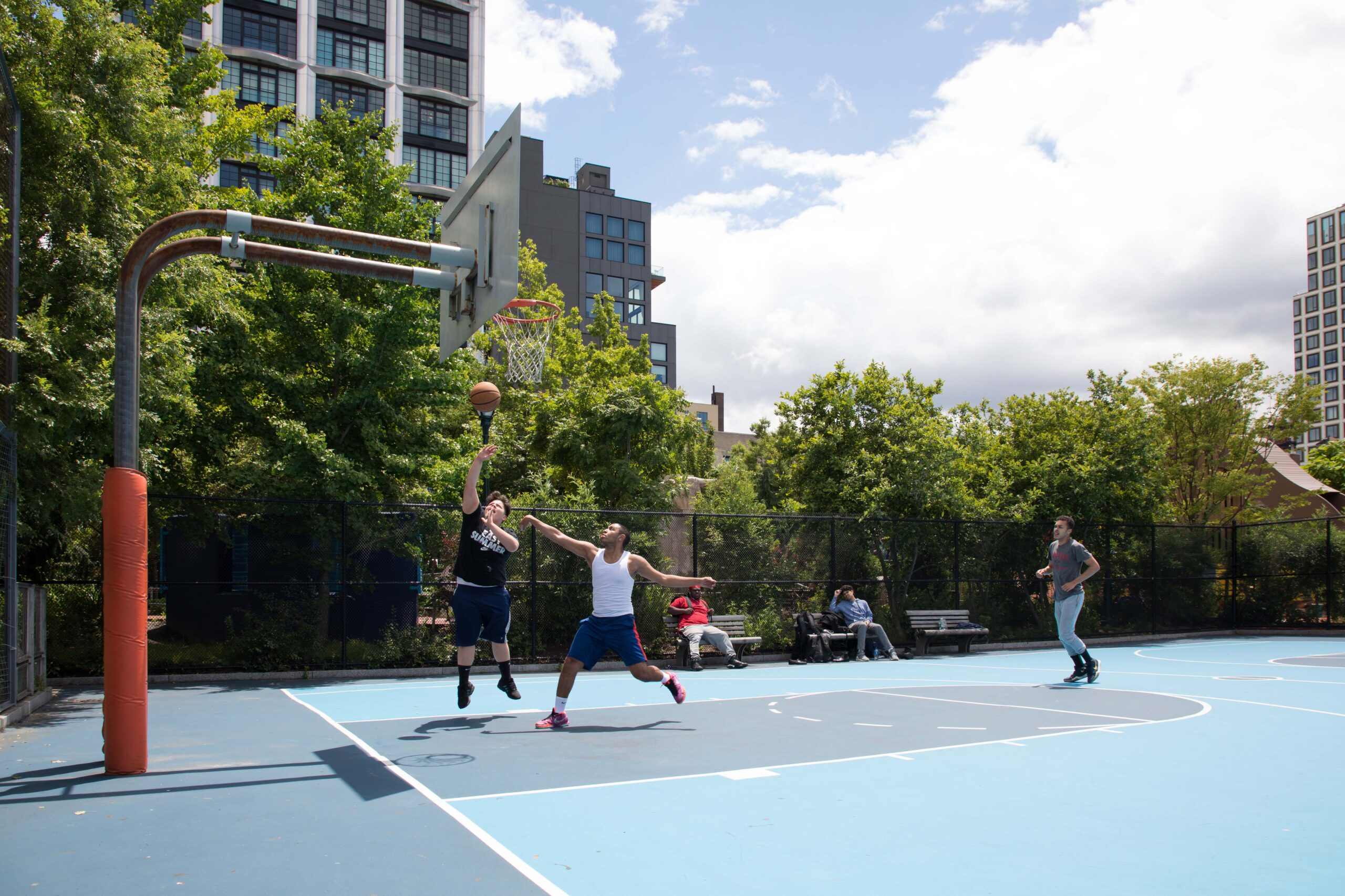 Basketball players shooting a basket during a game in Chelsea Waterside Park