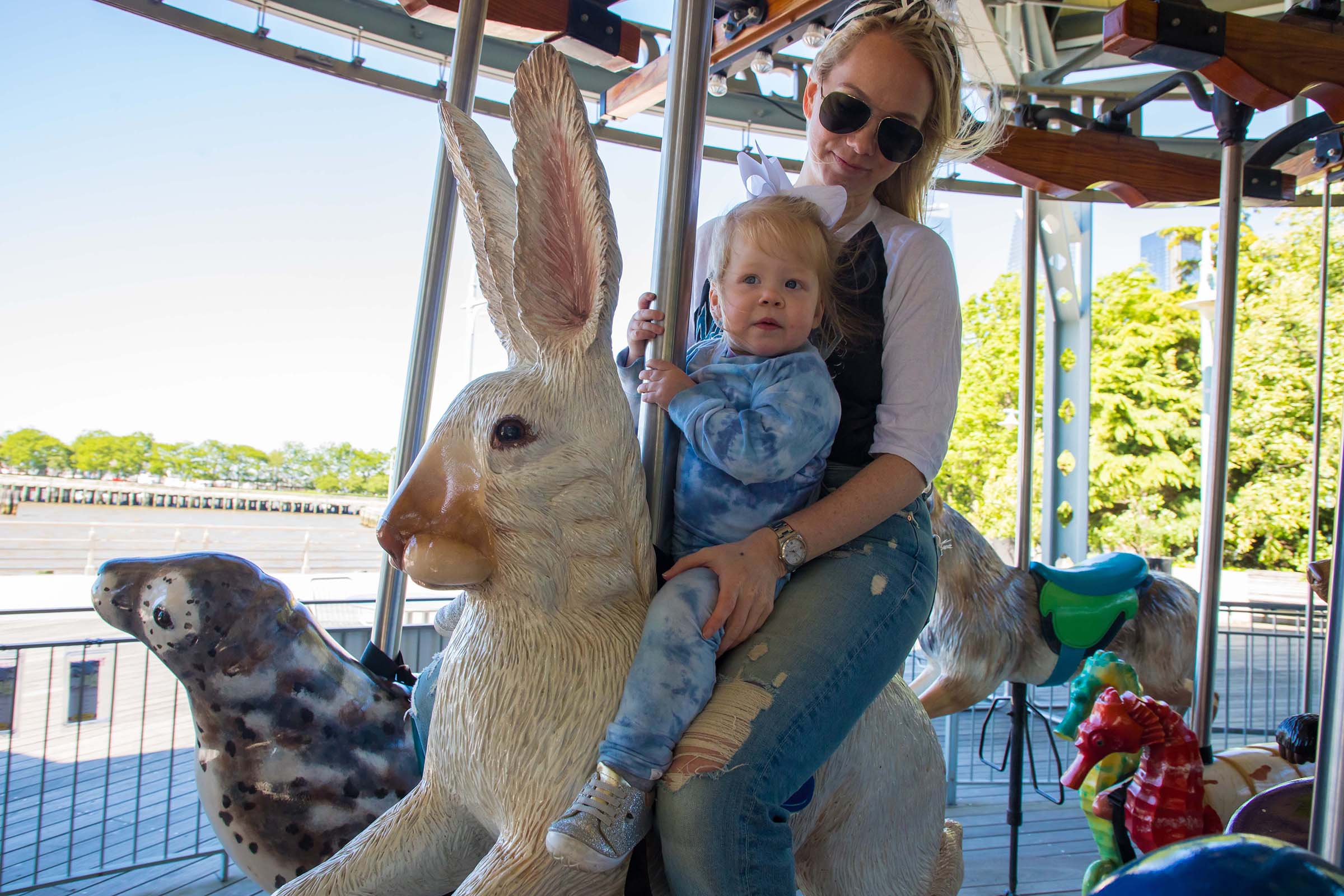 Kids and adults enjoy a ride on the carousel at Pier 62