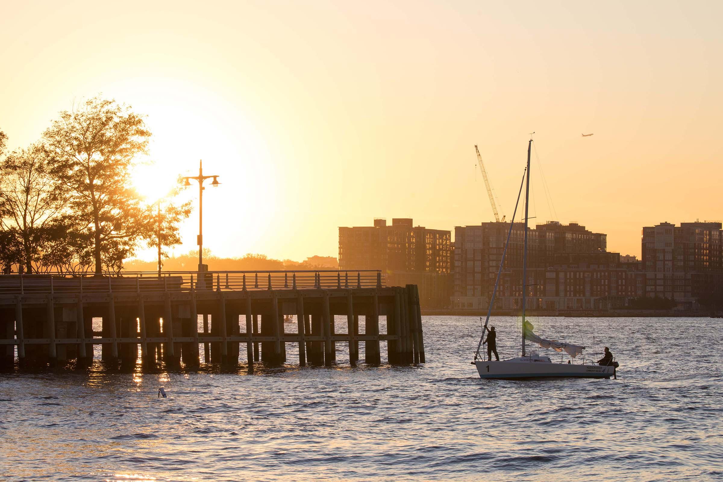 The sun sets as a sailor moors near Pier 64