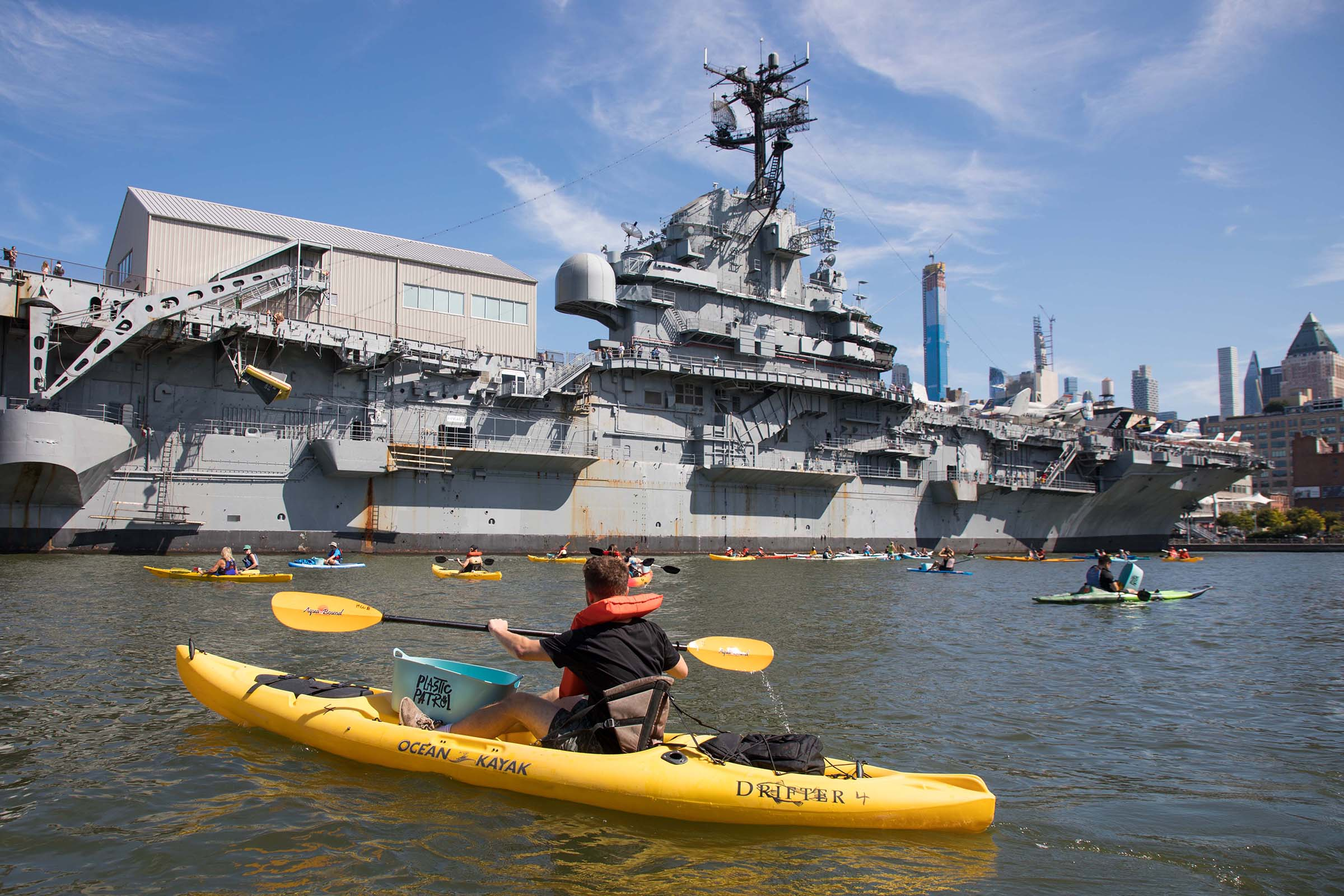 A kayaker looks on at the Intrepid vessel in the Hudson River