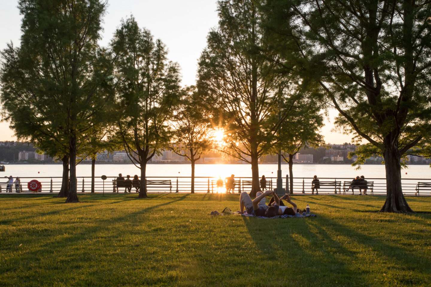 The sunsets as Park Visitors sit on the Clinton Cove lawn bowl