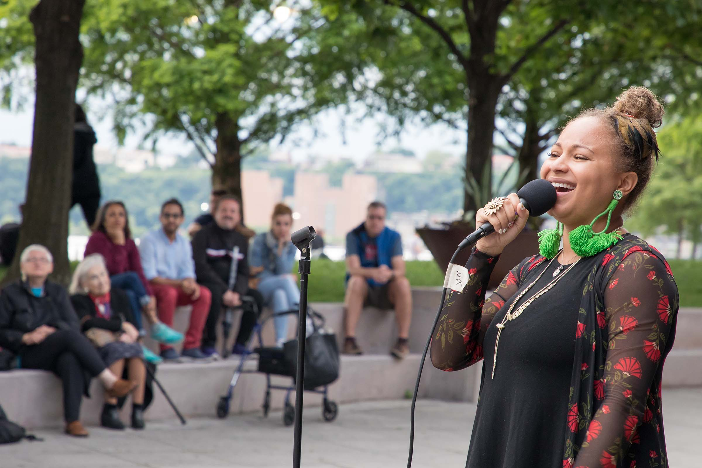Smiling, a jazz singer hits her notes as the audience watches