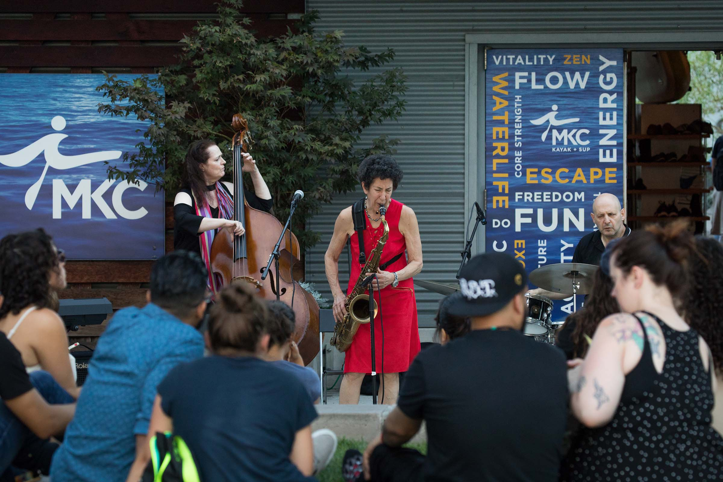 A lady in a red dress swinging with her tenor sax