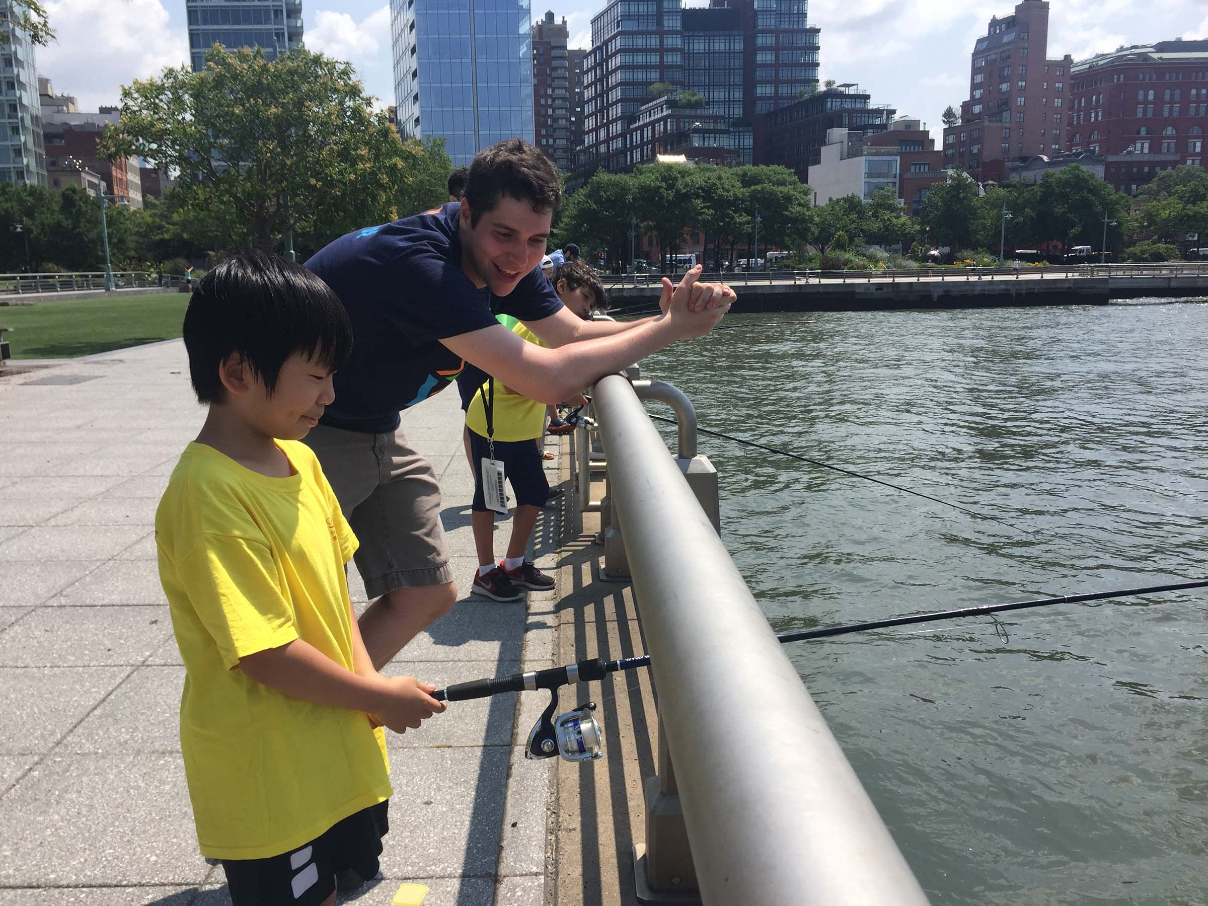 A happy kid fishes in the Hudson River
