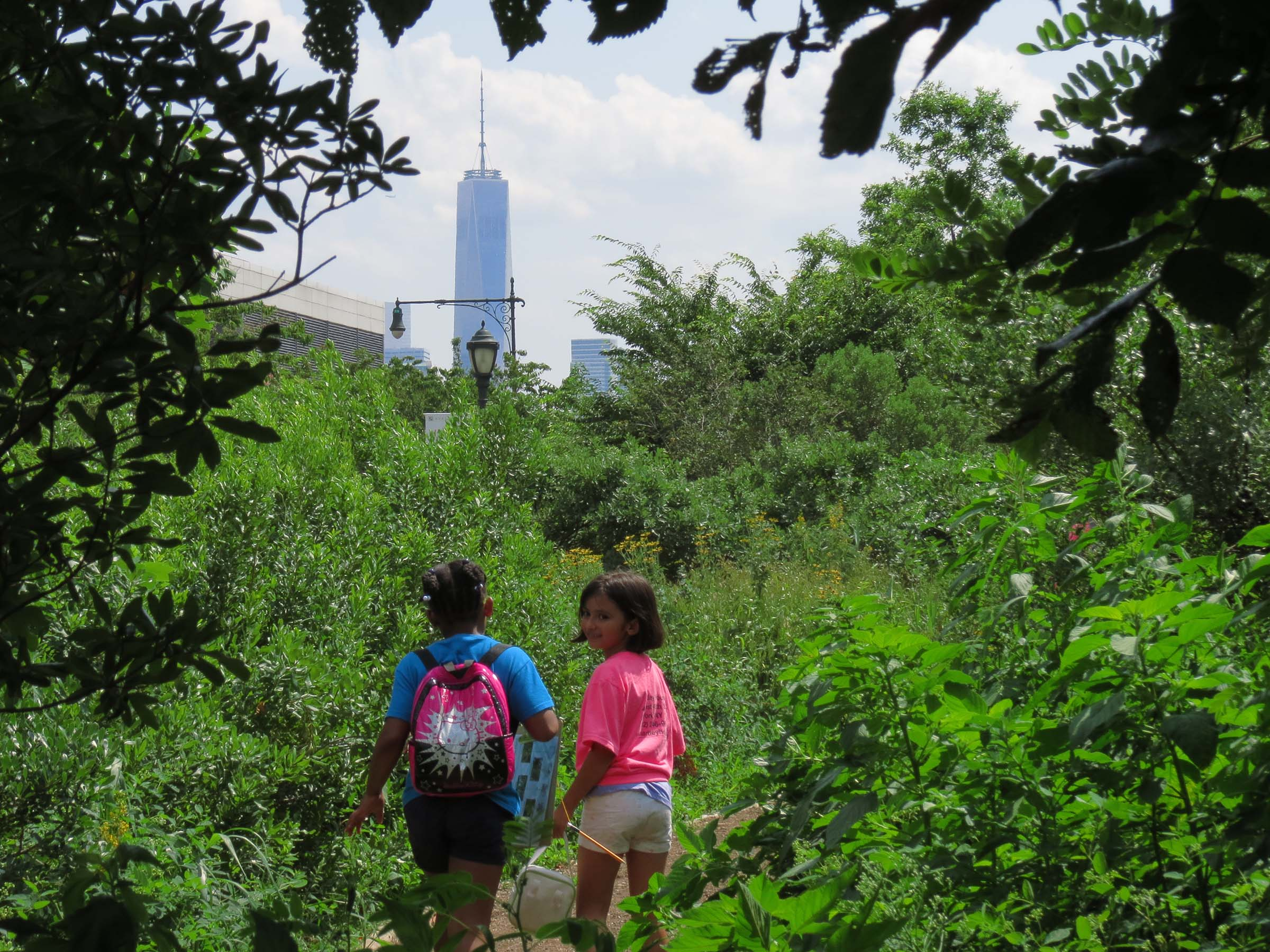 Two students walk through the greenery in the Tribeca Gardens