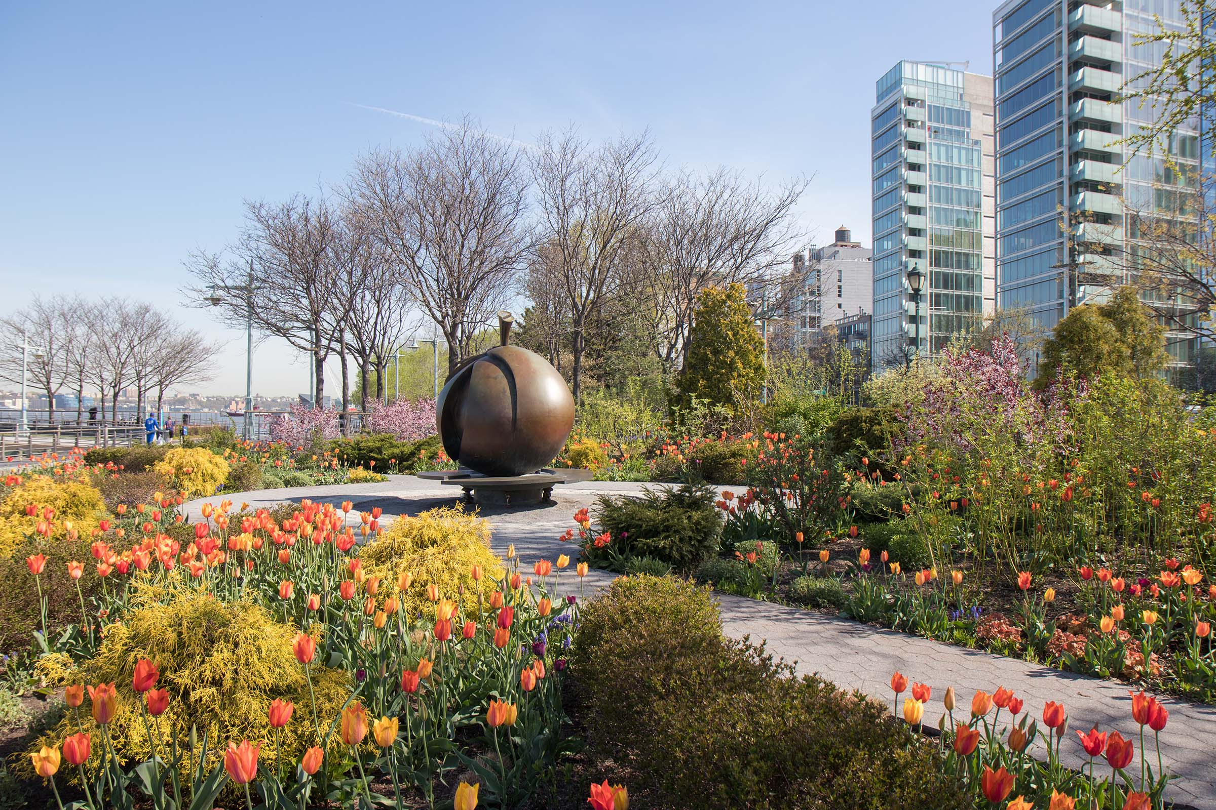 Lush green and yellow bushes and tulips circle the bronze Apple statue