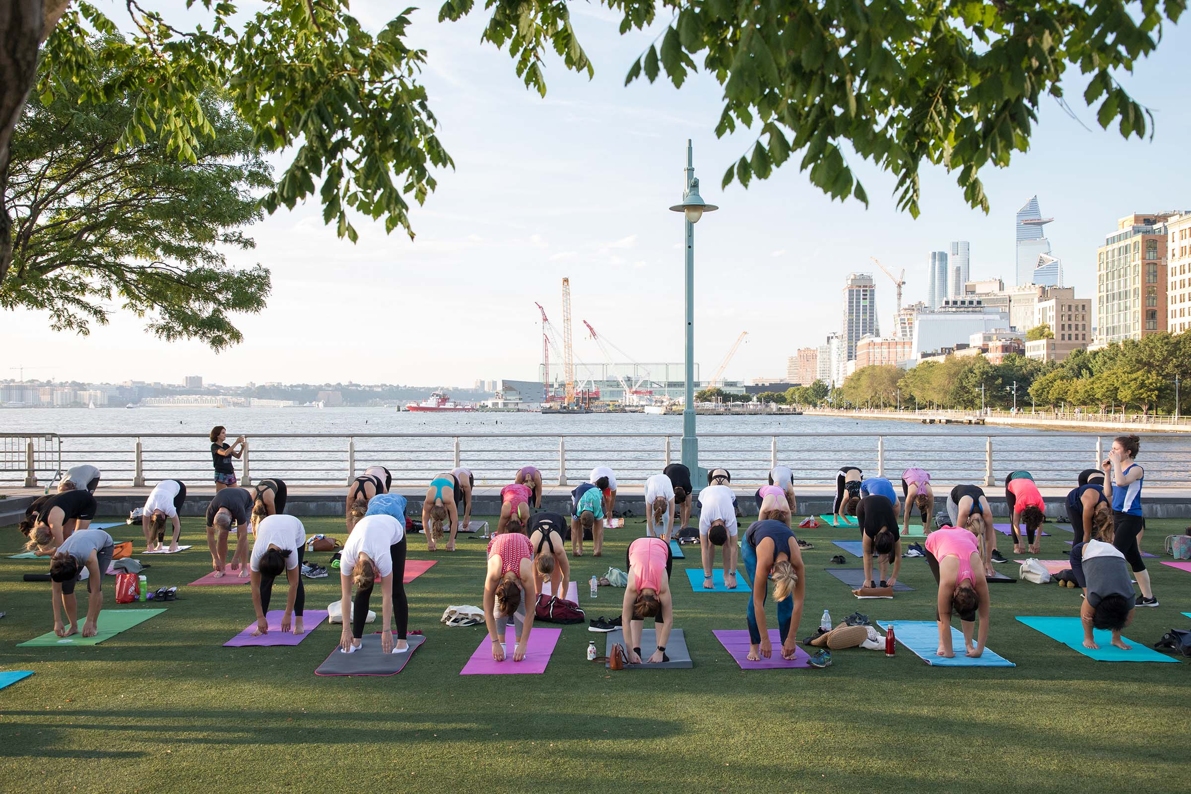 Participants at a yoga class on Pier 46 stretch and curve their backs