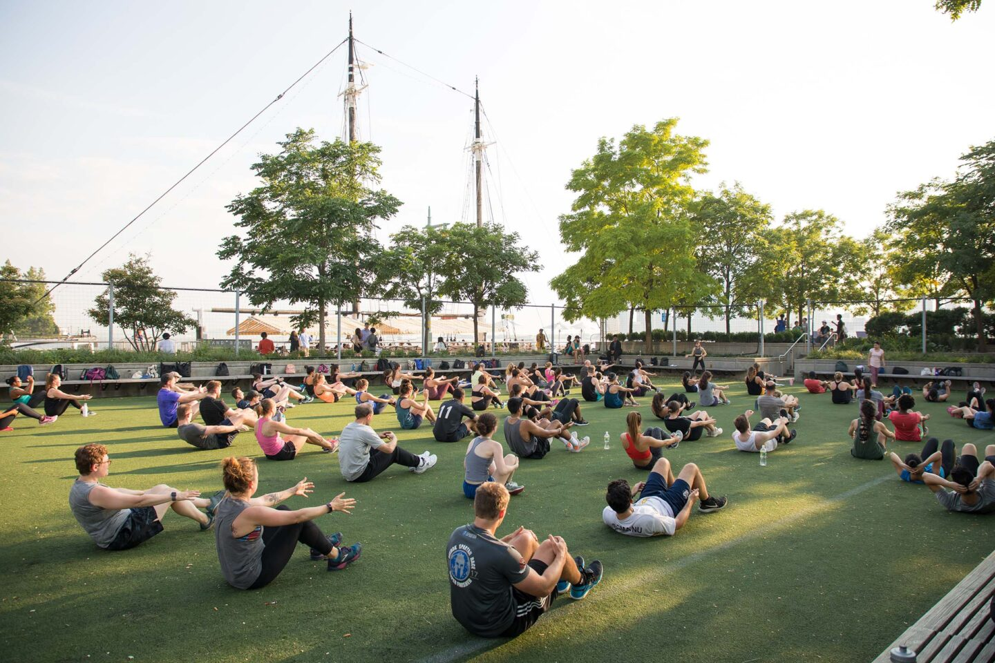 Participants at an exercise class practice crunches at Pier 25