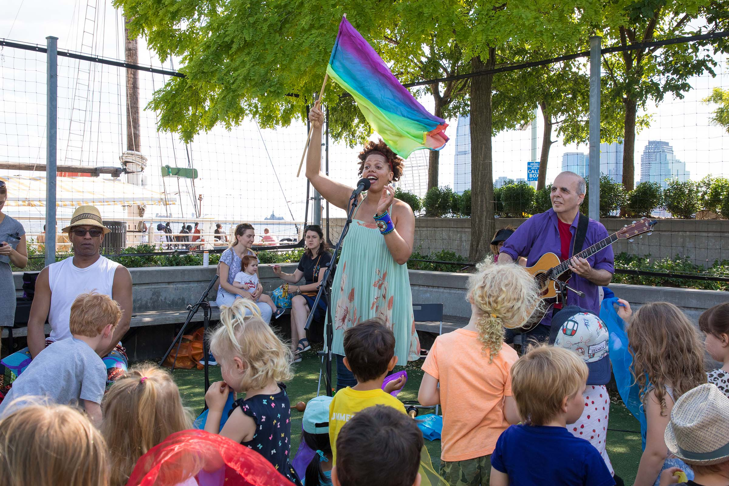 A rainbow flag is waving by the singer at RiverKids