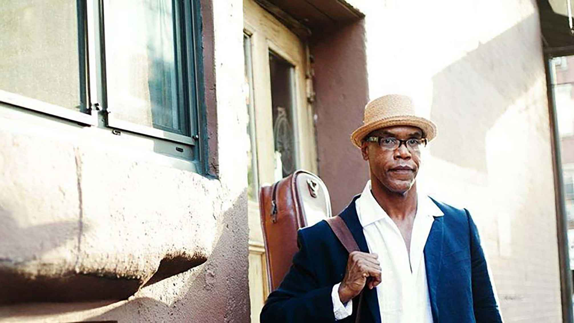Jazz musician Ed Cherry stands on a balcony with his leather cased guitar and hat
