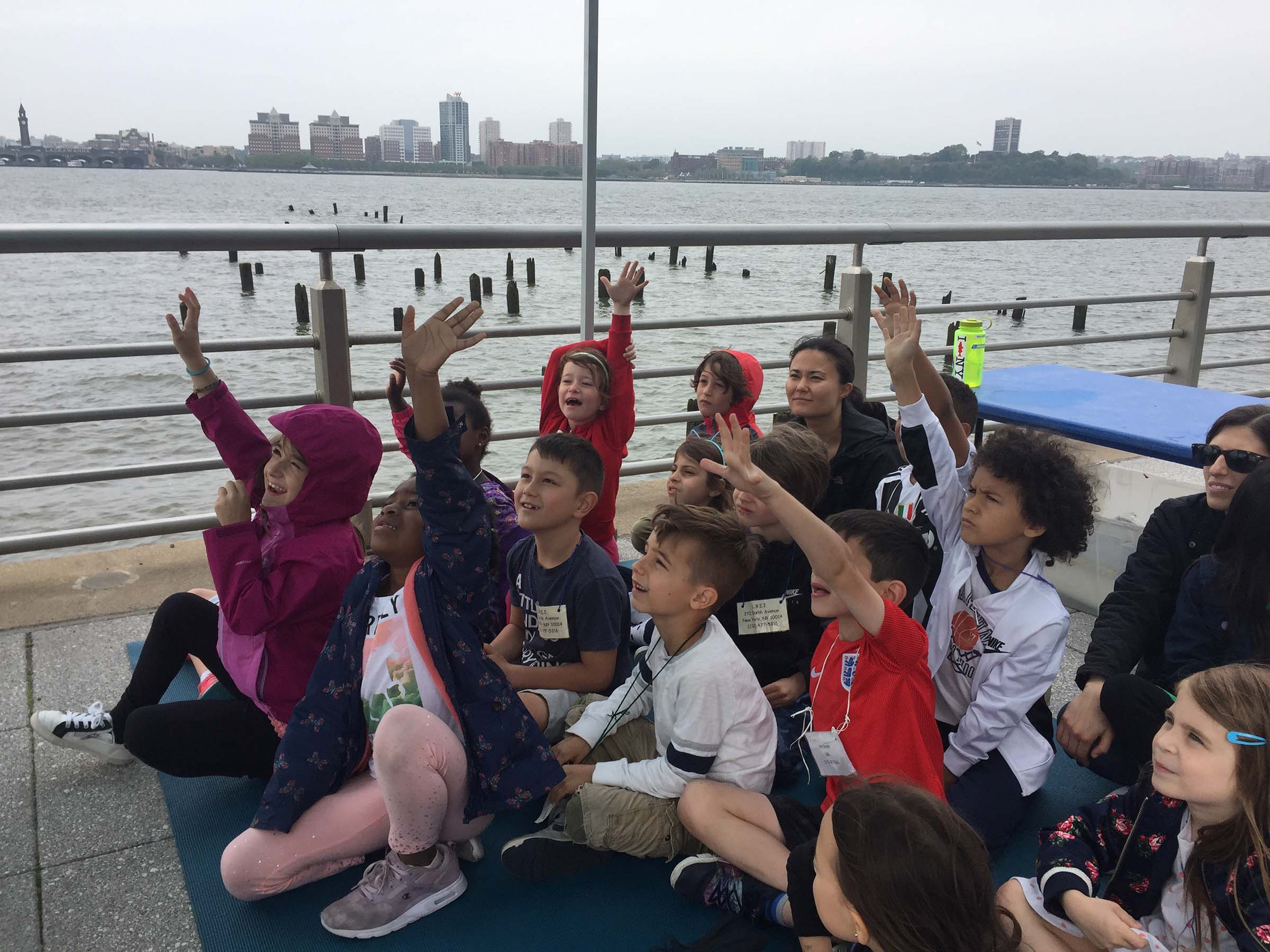 A group of students quickly raise their hands to answer the question about Hudson River Park