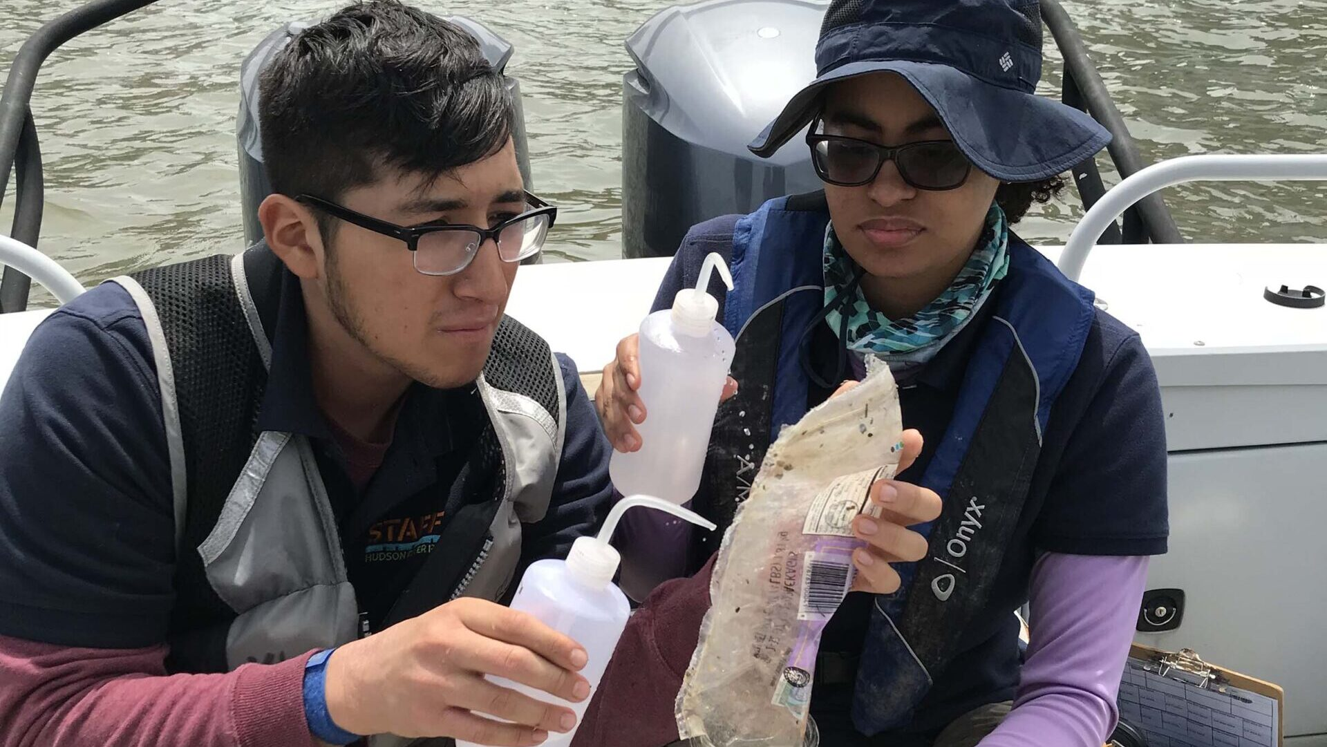 After pulling samples from the water, two scientists make observations