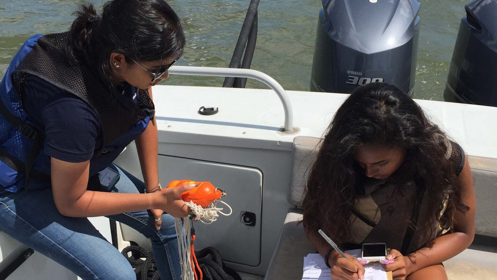 Scientists writing down their findings from a water sample on a boat
