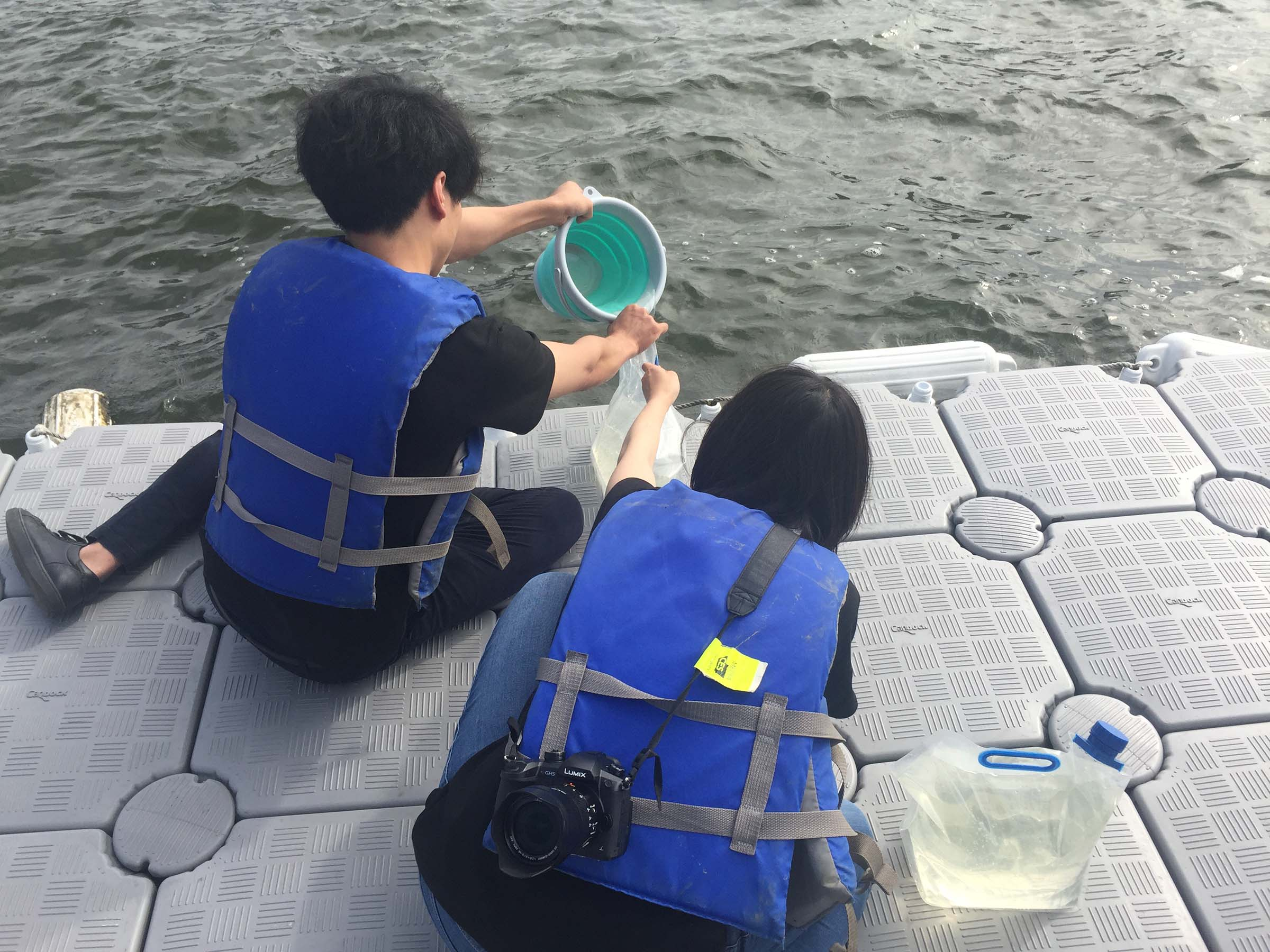 Students collecting water to use in their experiments from the Hudson River