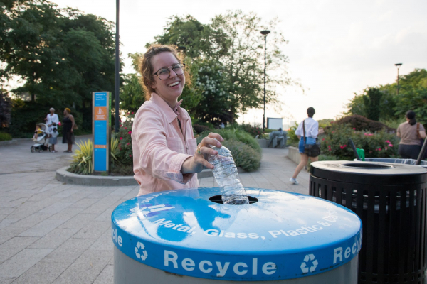 A Park visitor throws a plastic bottle into a recycling bin