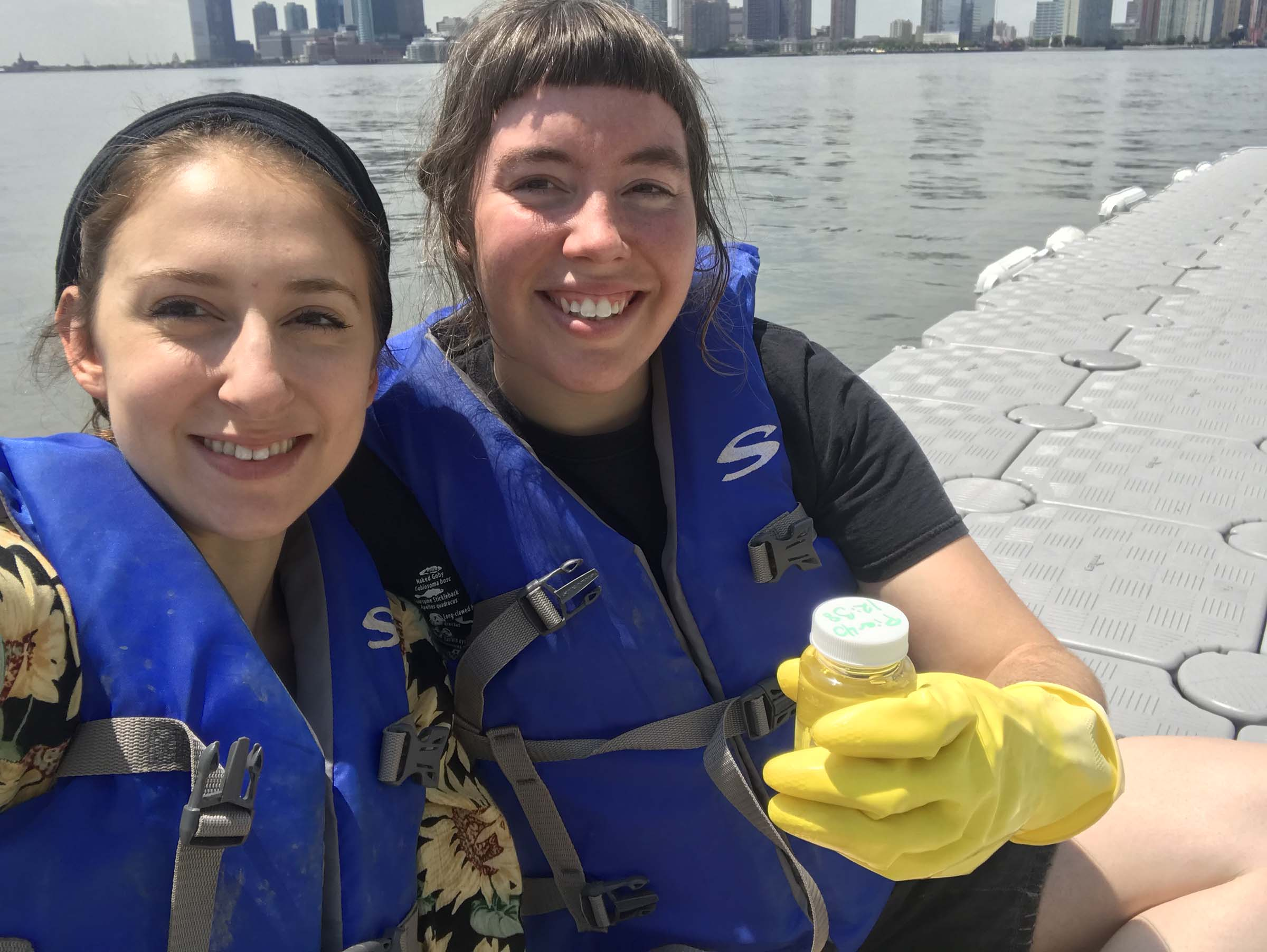 Two students smile at the camera as they hold their water specimen