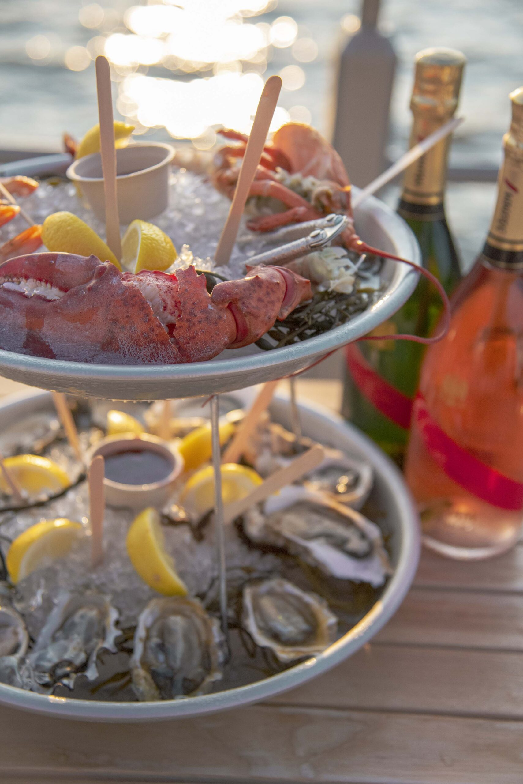 A tiered platter of seafood options with two bottles of sparkling wine to go with