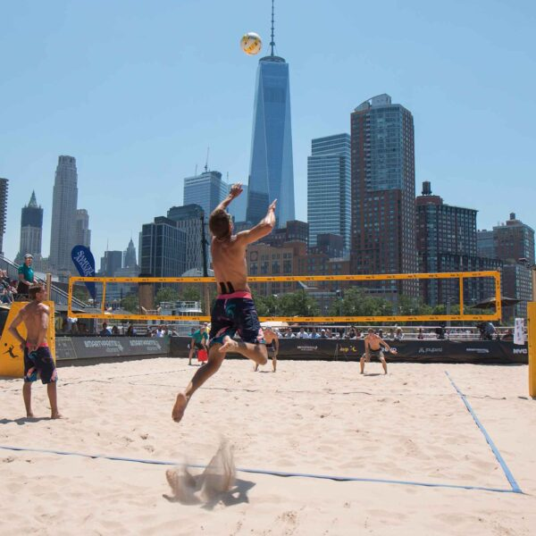A volleyball player jumps to hit the ball back at AVP in Hudson River Park