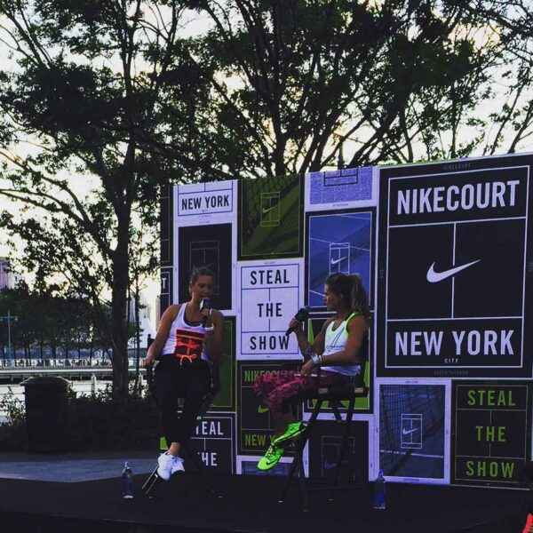 Two runners sit on a state and discuss running and other events