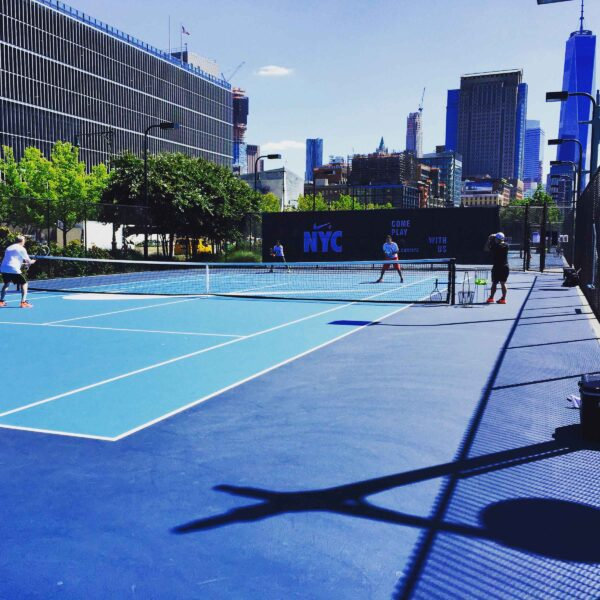 Two teams battle it out on the tennis courts in Hudson River Park