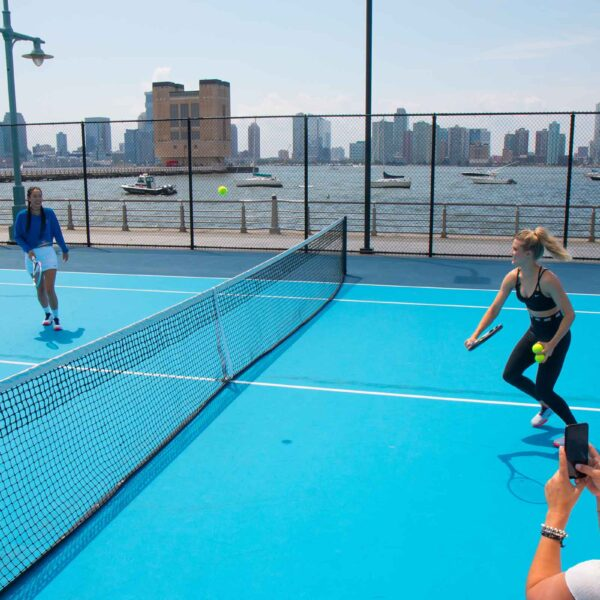 Running for the serve on the tennis courts in Hudson River Park