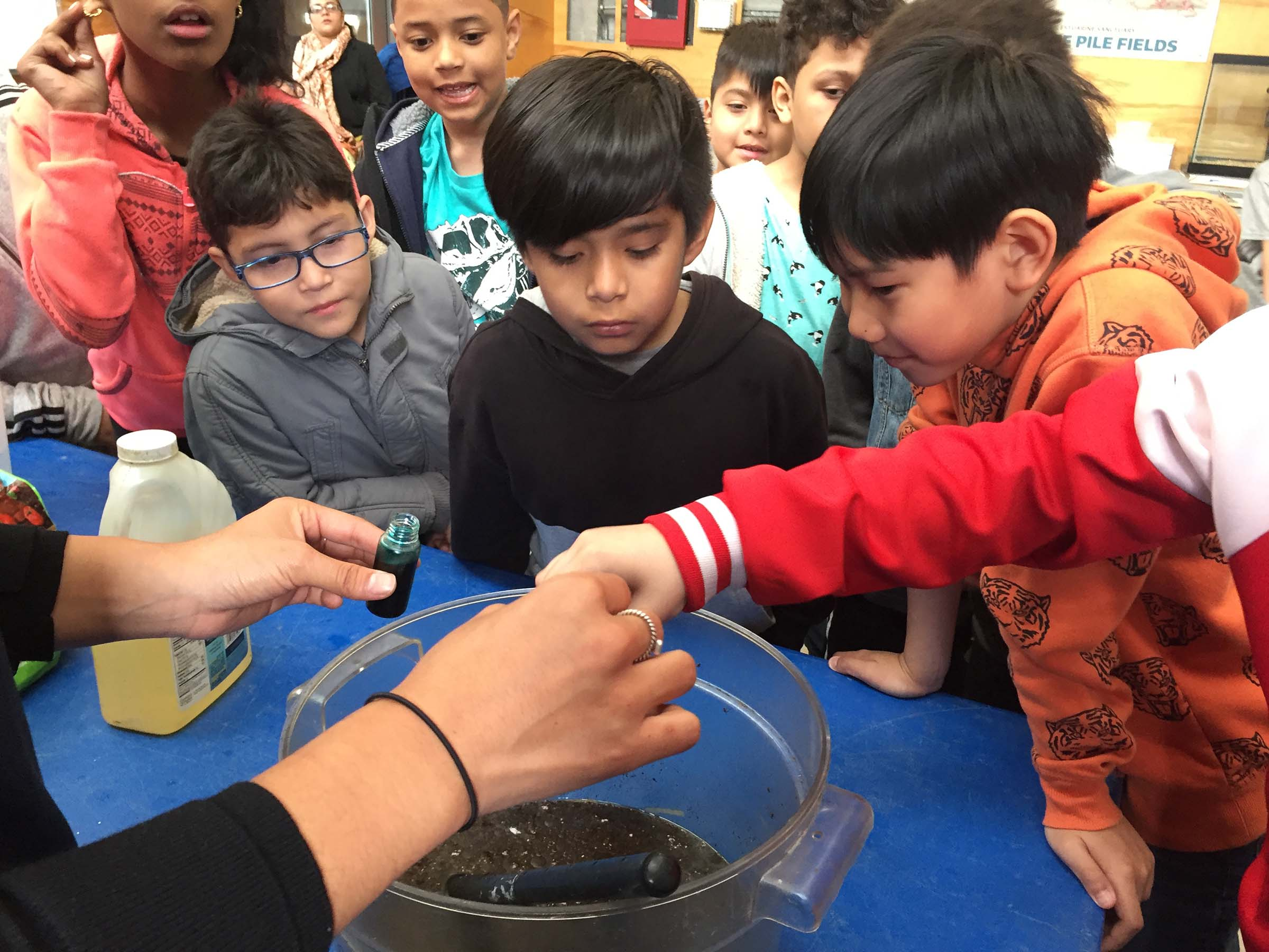 Students look at a makeshift pollution bucket