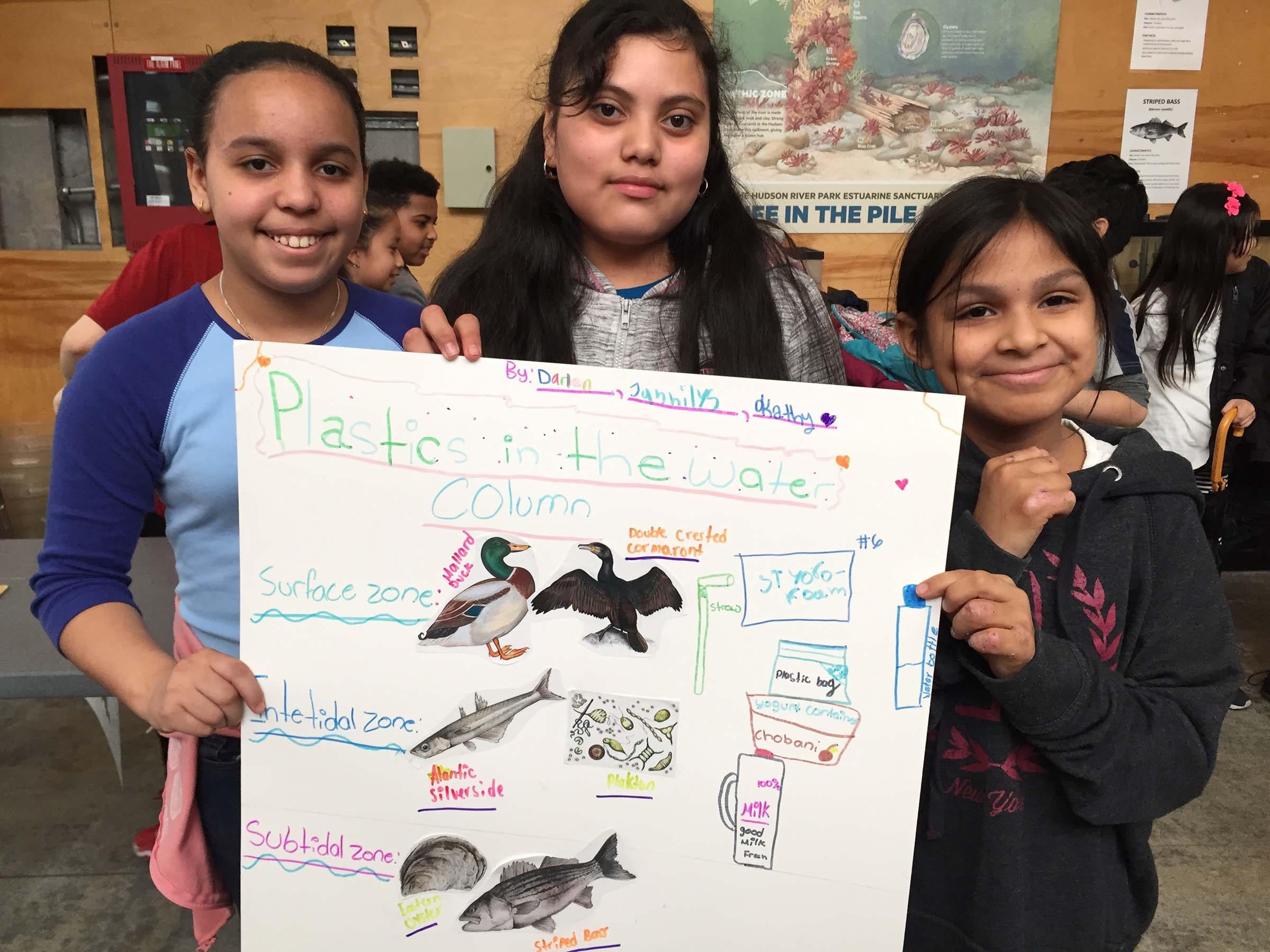 Students show their poster with animals from the Hudson River and how to stop pollution