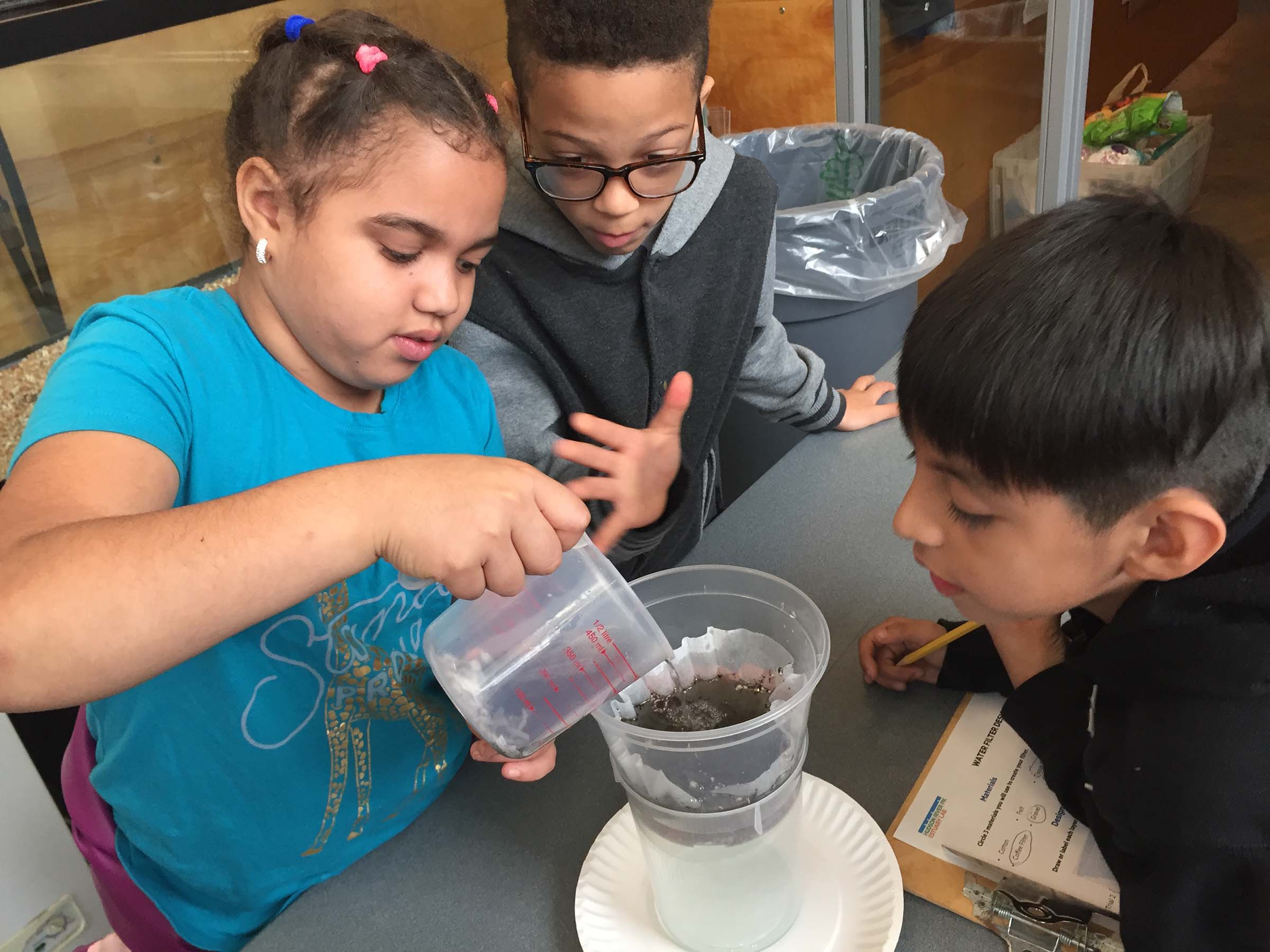 Students work on a project and pour water into a coffee filter with dirt