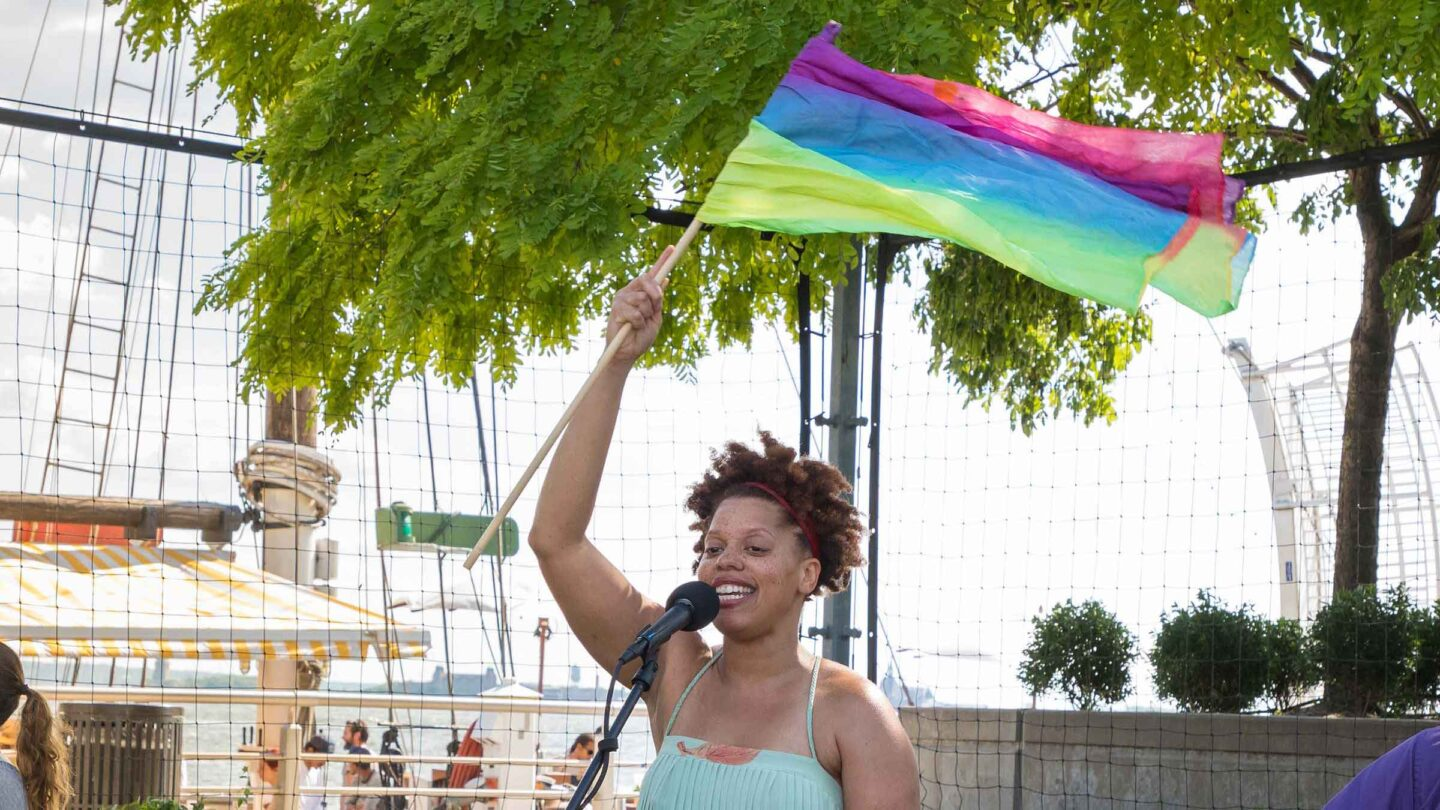 A rainbow flag is swinging back and forth as Sweetbeatz since to a crowd of kids