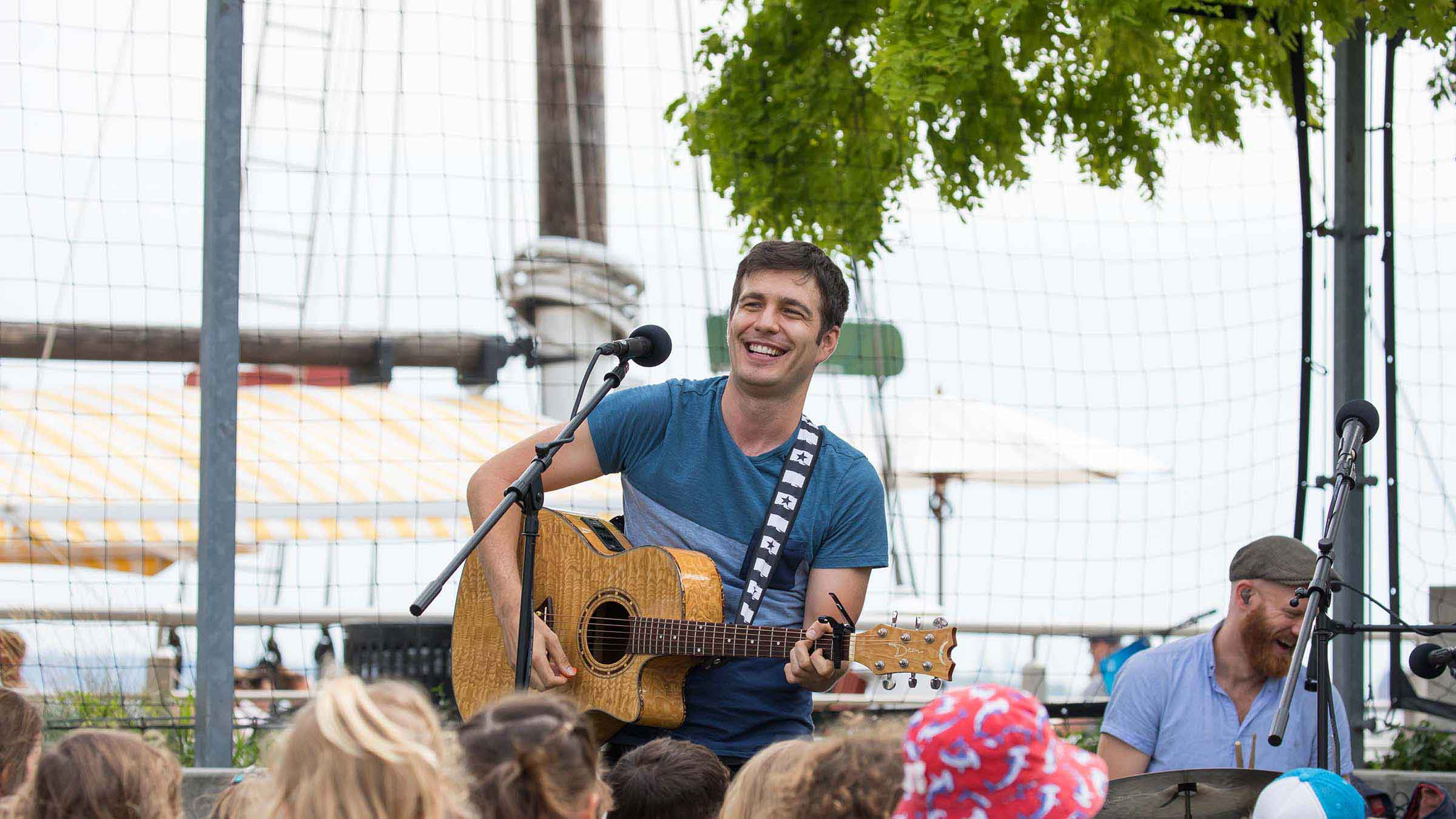 Tim Kubart strums a guitar and smiles at the audience