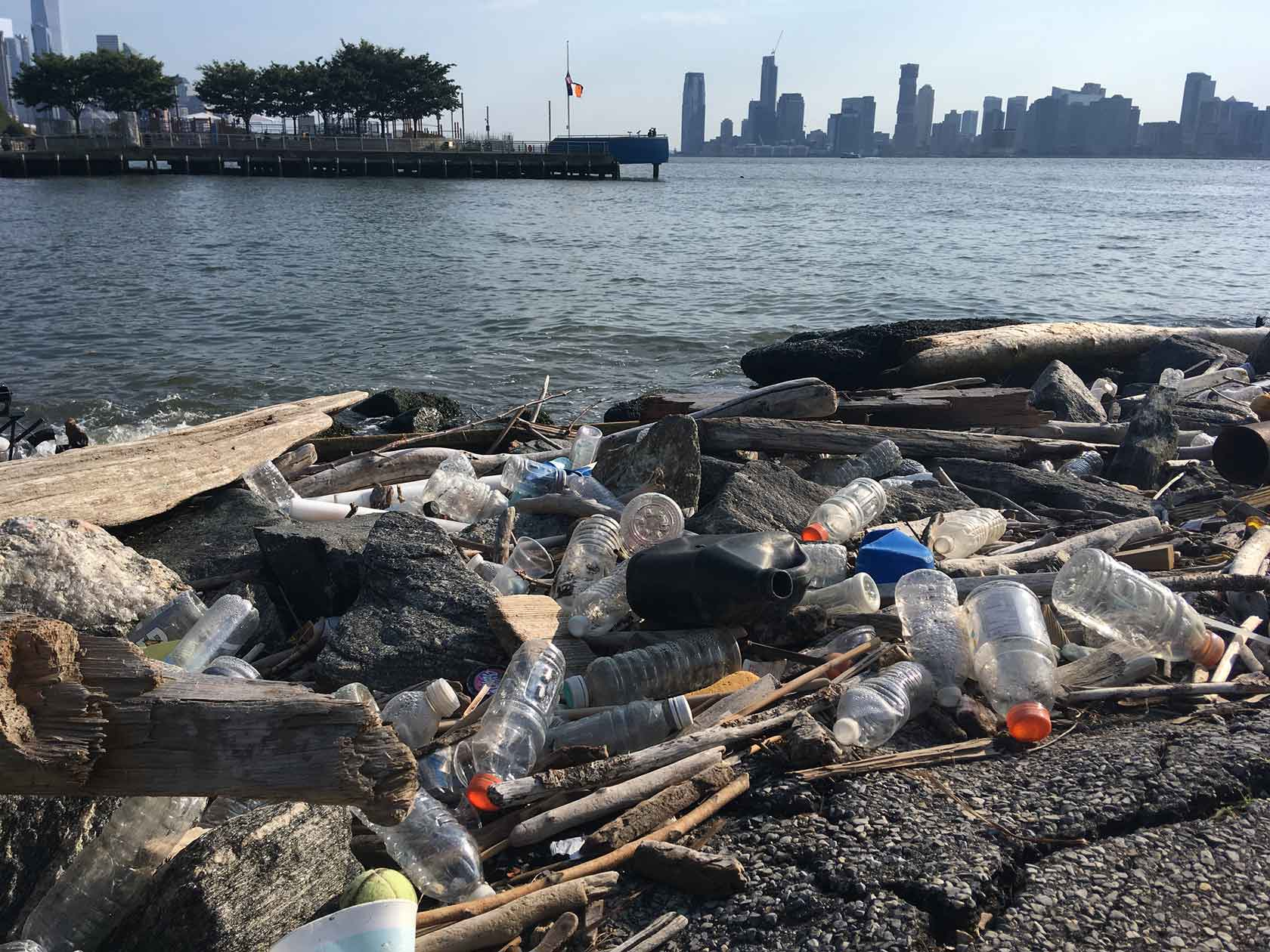 Plastic bottles and bags sit on the end of Gansevoort Peninsula