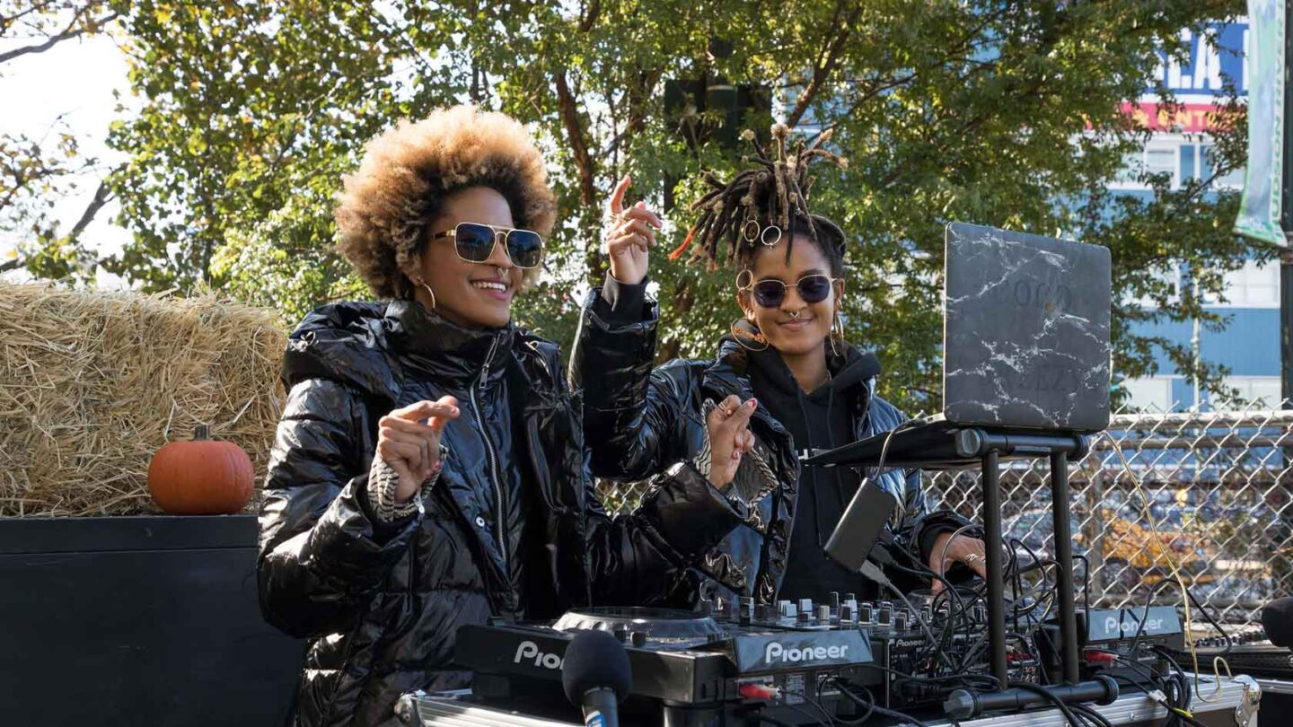 DJ's Coco and Breezy dressed in black jackets play music for the crod