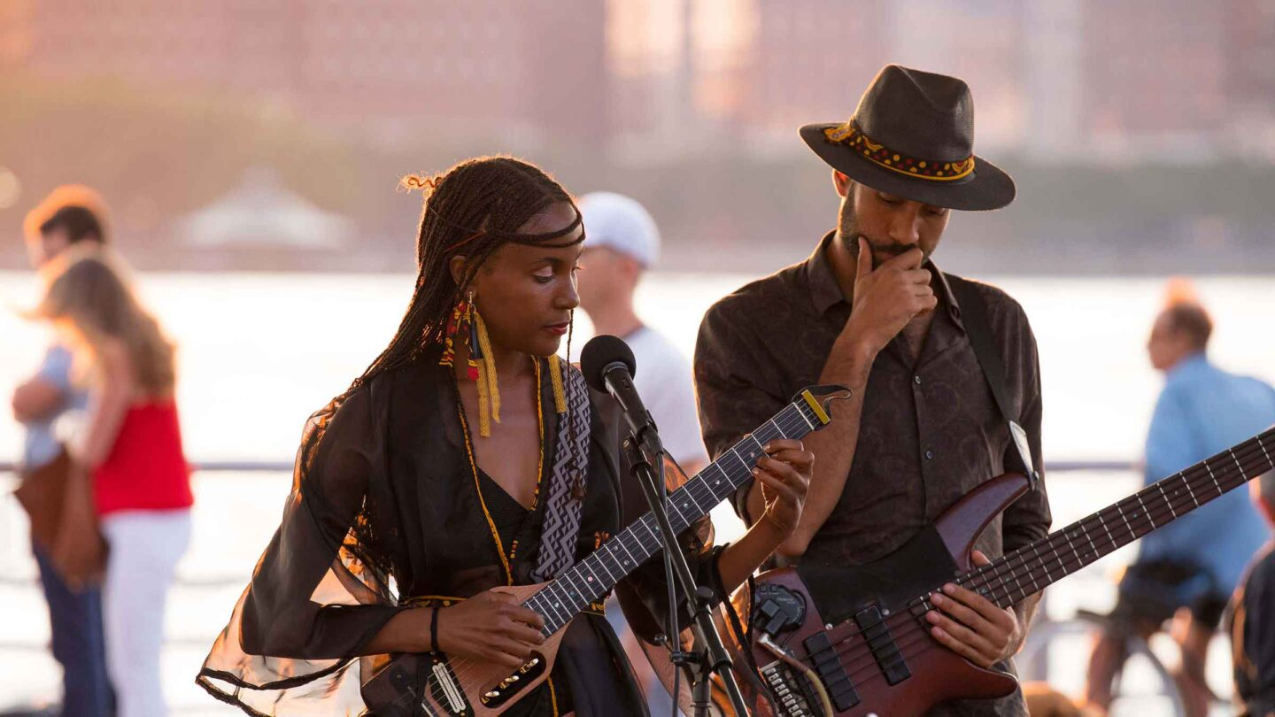 Duo Koku Gonza perform as the sunsets in the distance. Both strum guitars