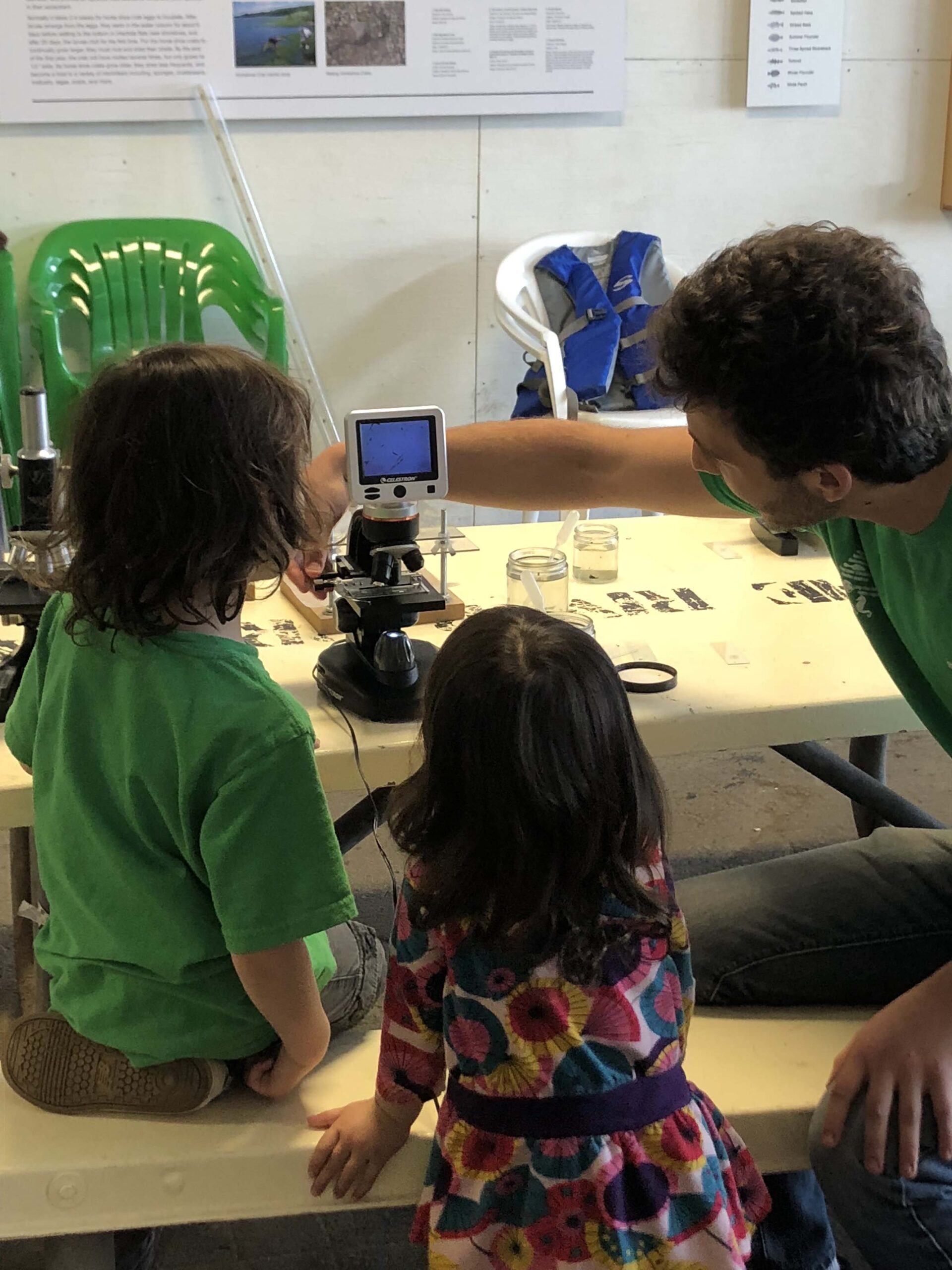 In the wetlab, two children look at the microscope at the findings from the day