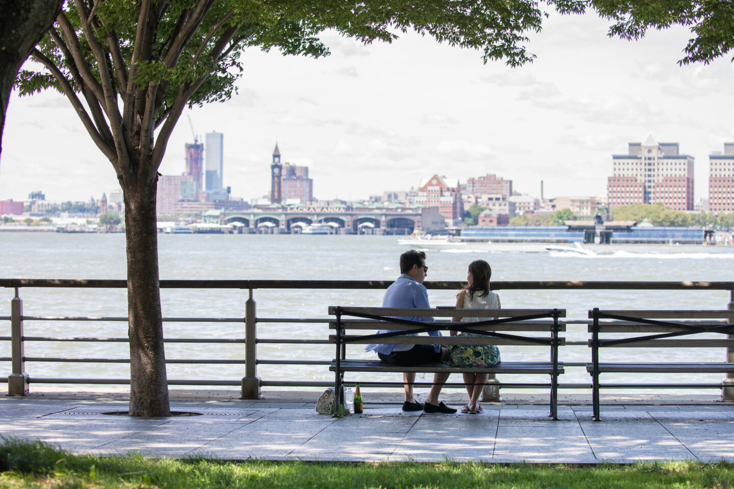 Two park visitors sit on a bench looking out to the hudson river