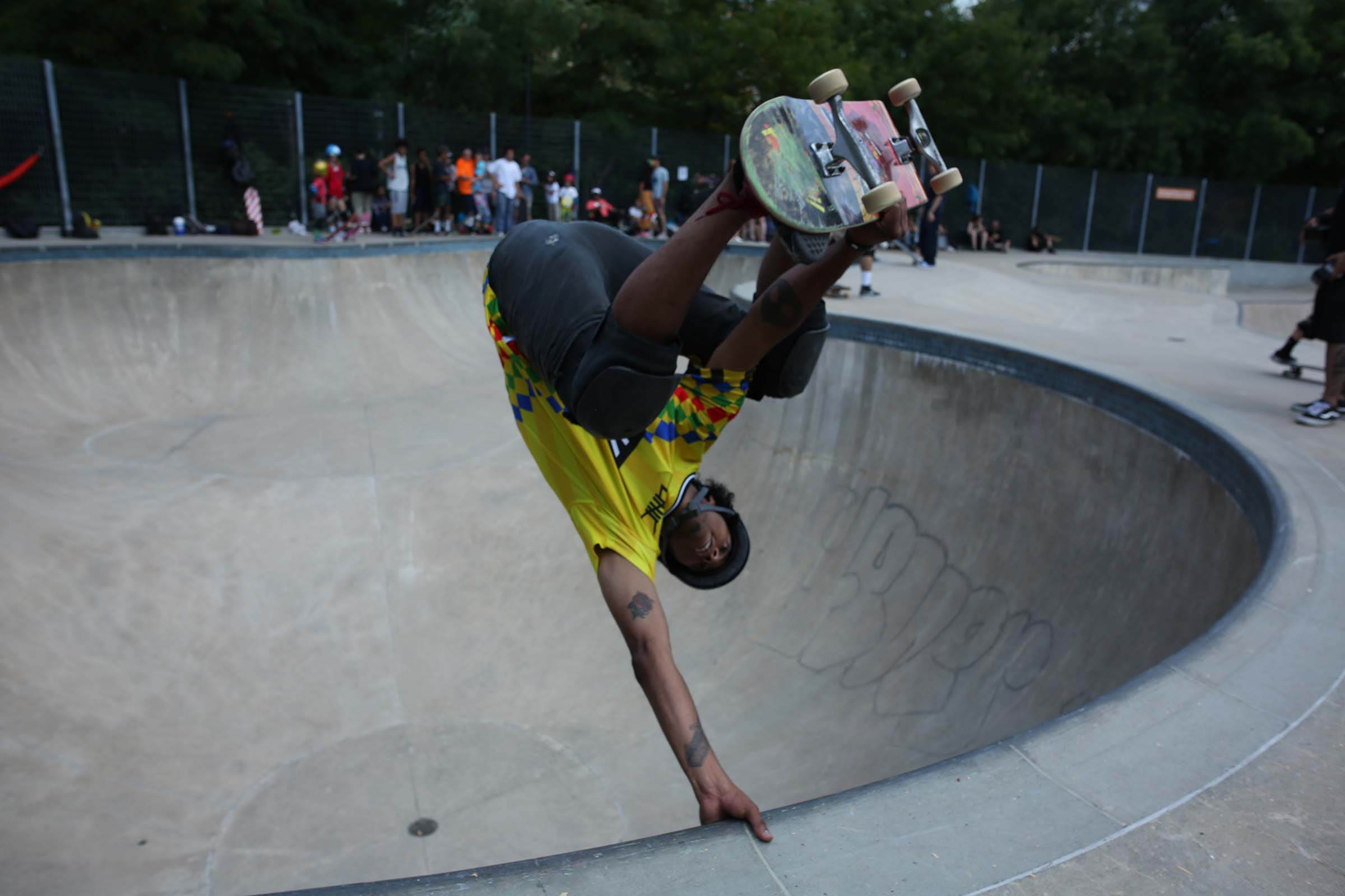 A skateboarder flies upside down and grabs the rim of the bowl