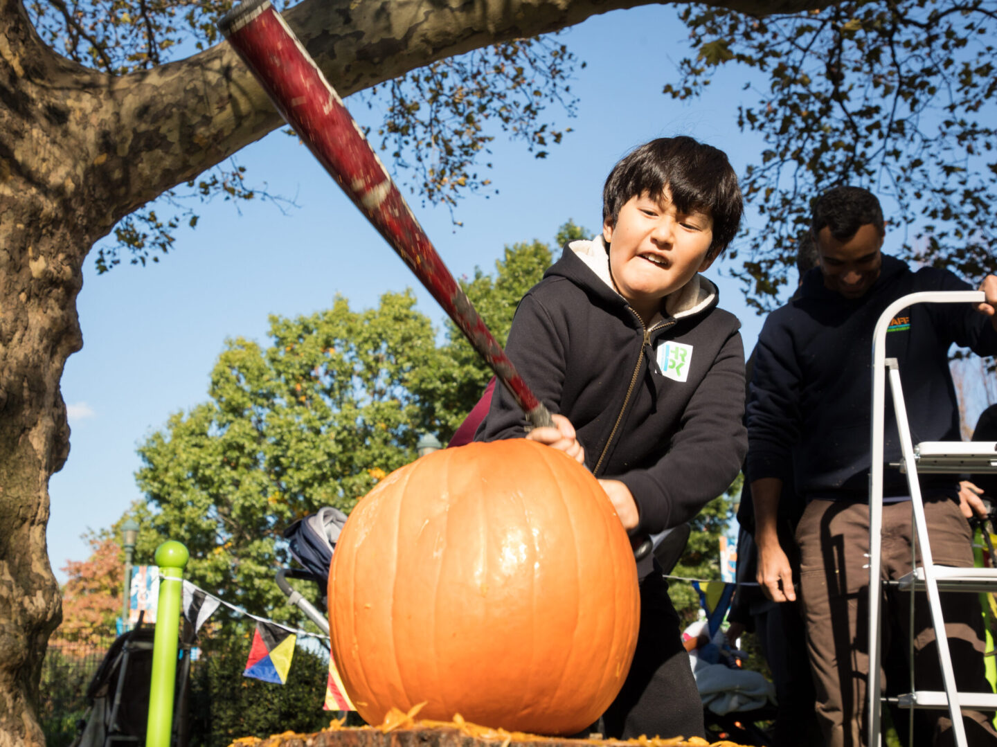 A kid readies his swing to smash the pumpkin