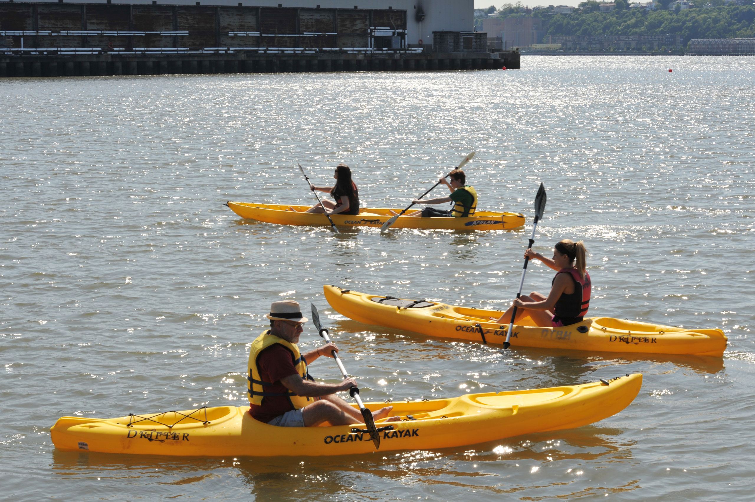 Park patrons paddle yellow kayaks in the Hudson River from the Pier 96 Boathouse